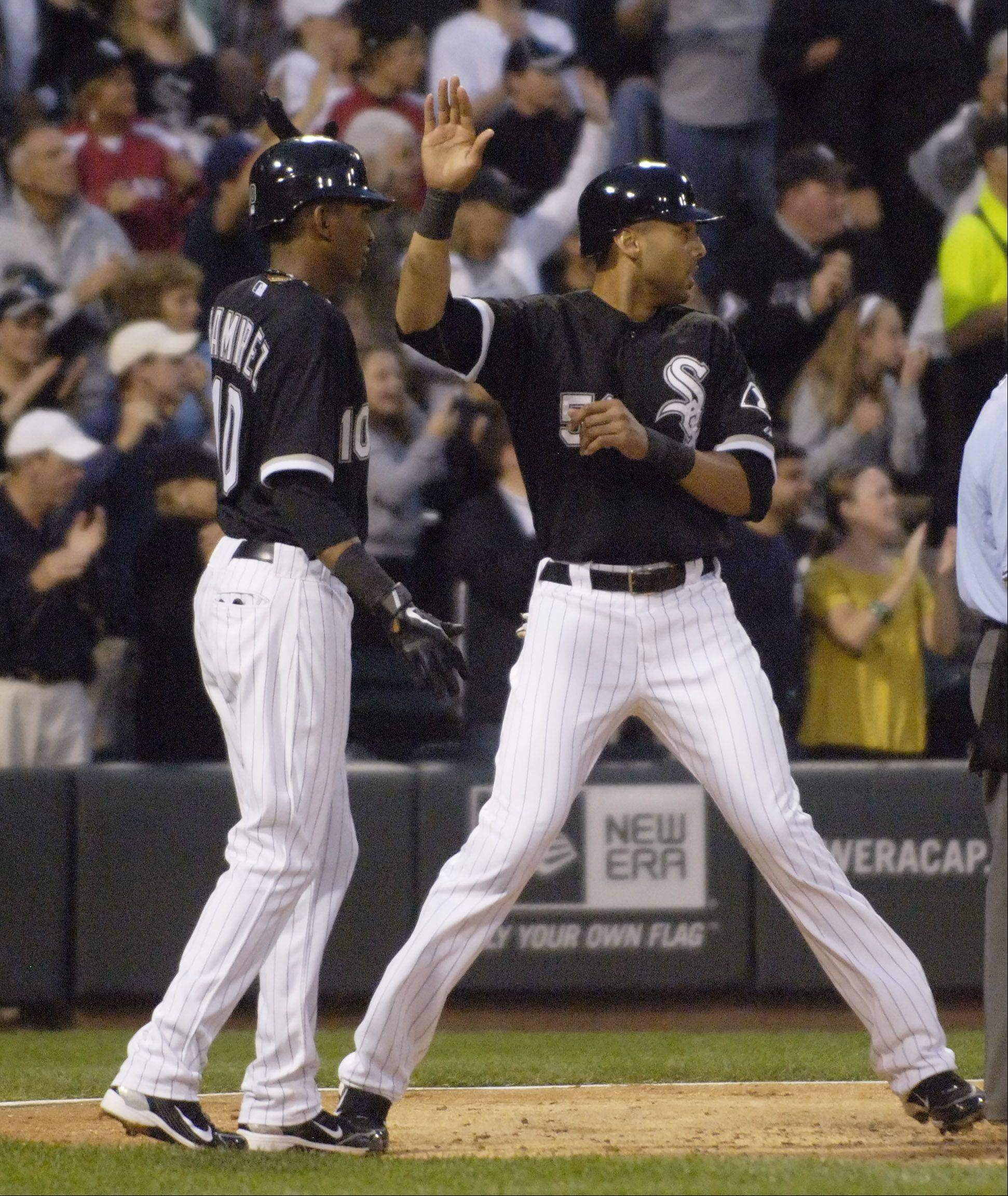 Alexei Ramirez, left, and Alex Rios greet one another at the plate after scoring on A.J. Pierzynski's triple during Wednesday's game against the Cubs at U.S. Cellular Field.