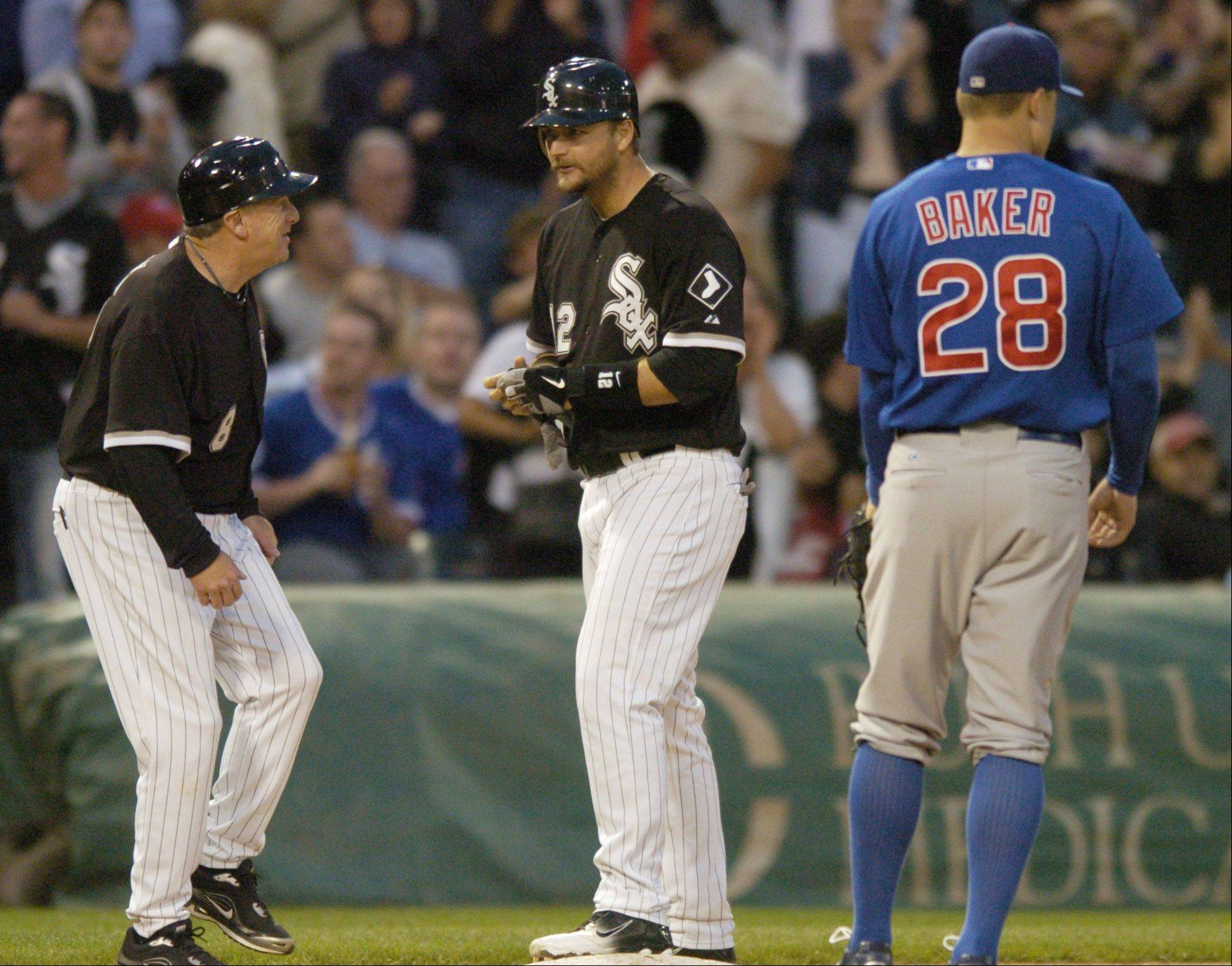 A.J. Pierzynski of the Sox chats with third base coach Jeff Cox after hitting a two-run triple as Cubs third baseman Jeff Baker Stands by the bag during Wednesday's game at U.S. Cellular Field.