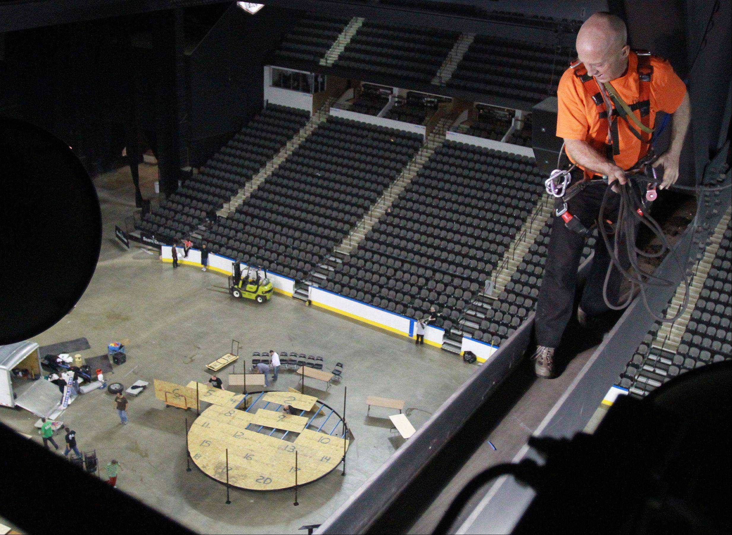 Sixty-two year-old Tom Russeli of Mt. Prospect walks across a beam 70 feet above the main floor of the Sears Centre at midnight.