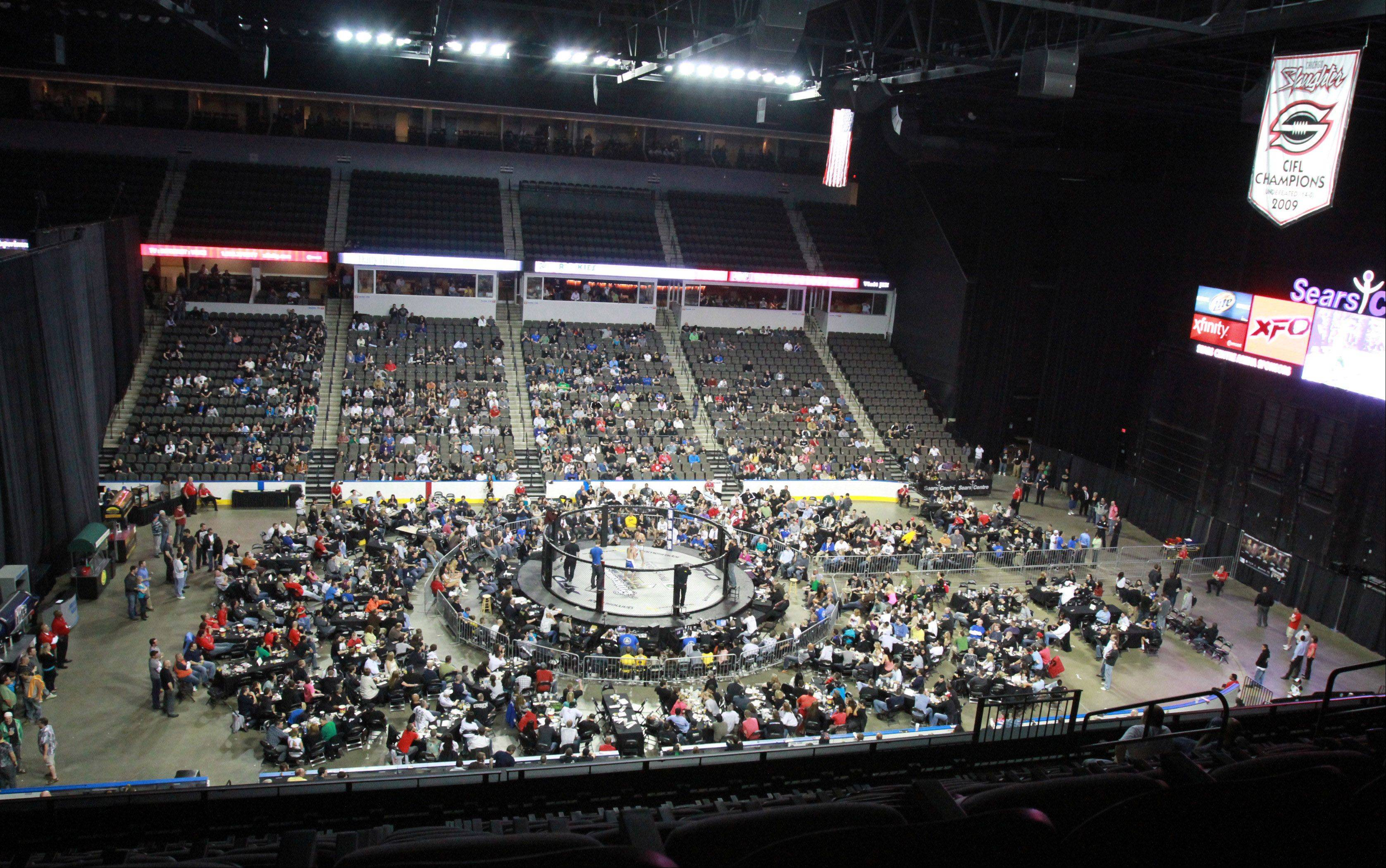 The Sears Centre crowd is entertained by a mixed martial arts cage match, but in a matter of hours the crowds will be gone and the arena floor will be transformed into a football field.