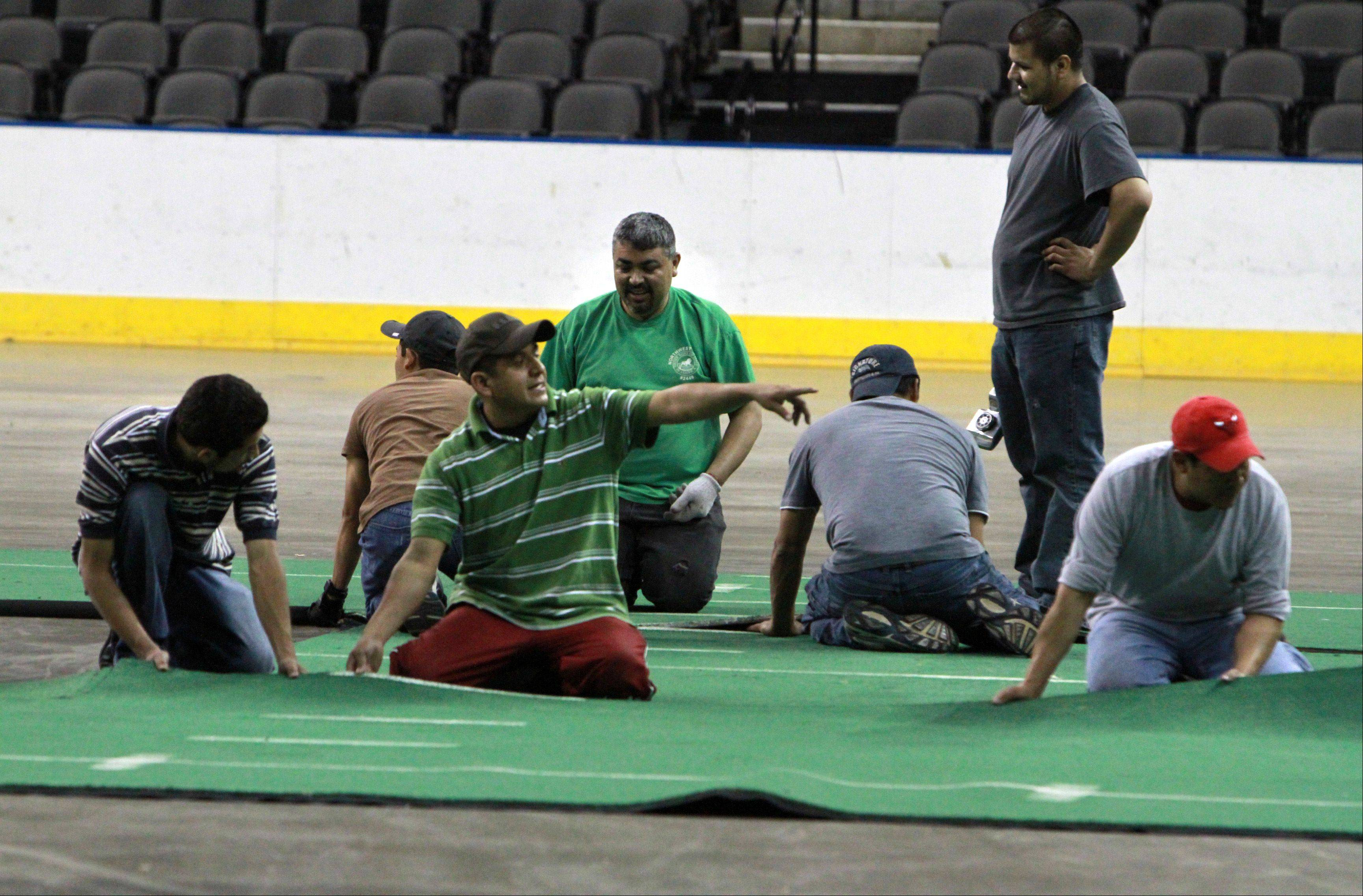 Fifteen Sears Centre employees stretch out the first sections of the 85 by 202 feet of indoor turf at 2:30 a.m. Saturday.
