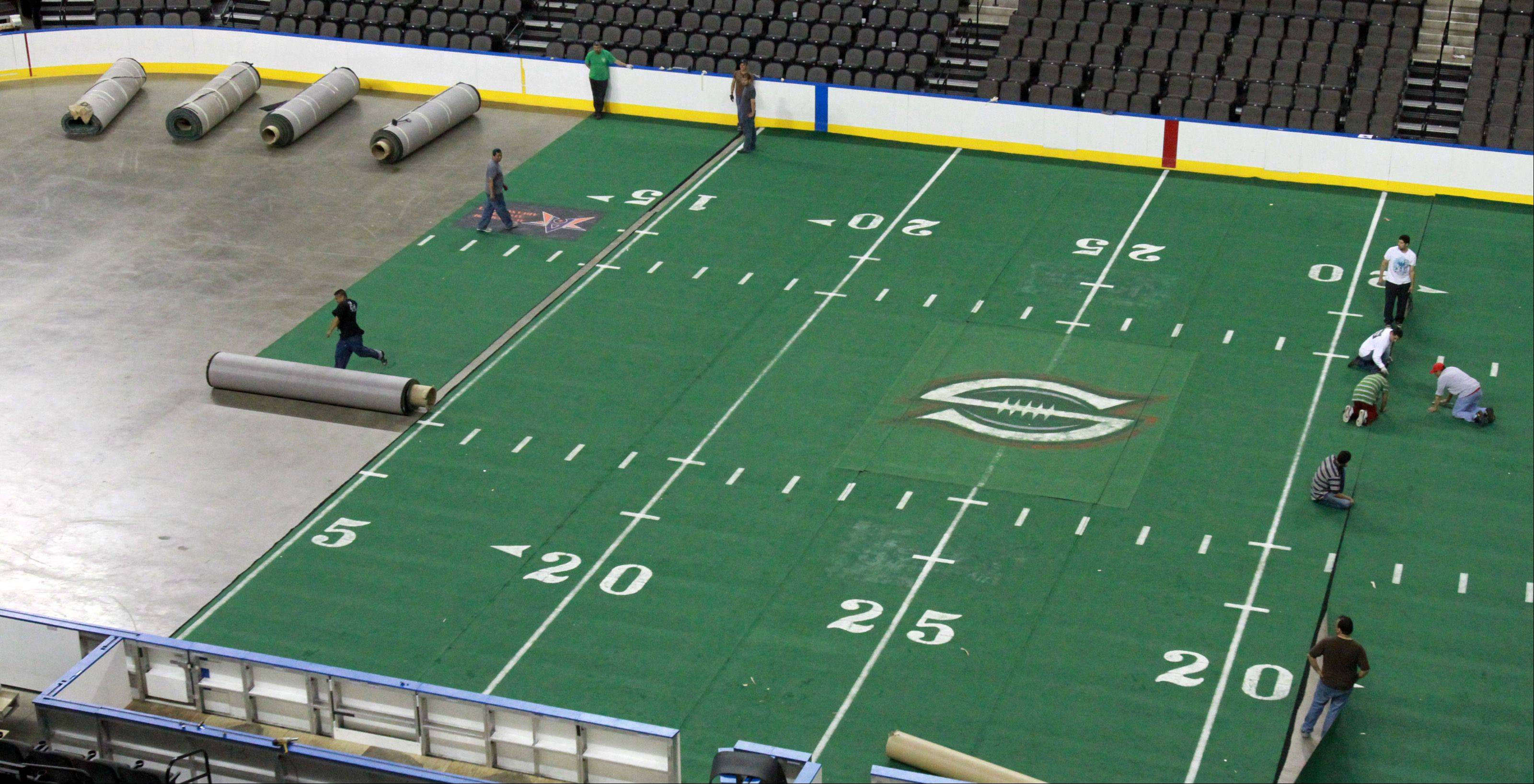 Workers begin to roll out the last sections of the 85 by 202 feet of indoor turf.
