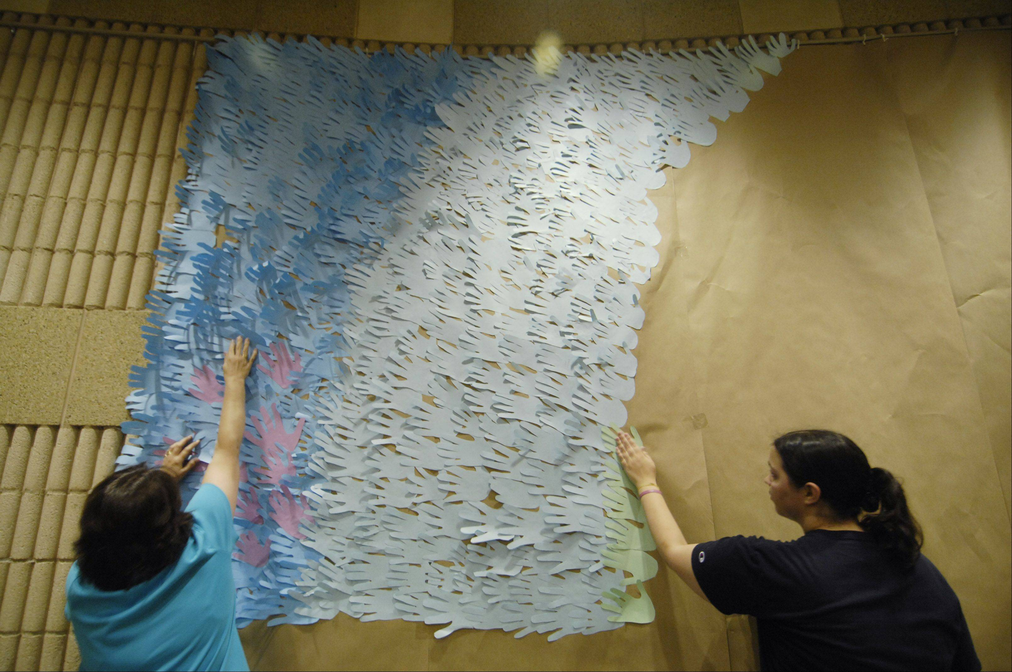 Volunteers work on a mosaic made of parishioners traced hands for the 100th anniversary of St. Peter Church in Geneva.