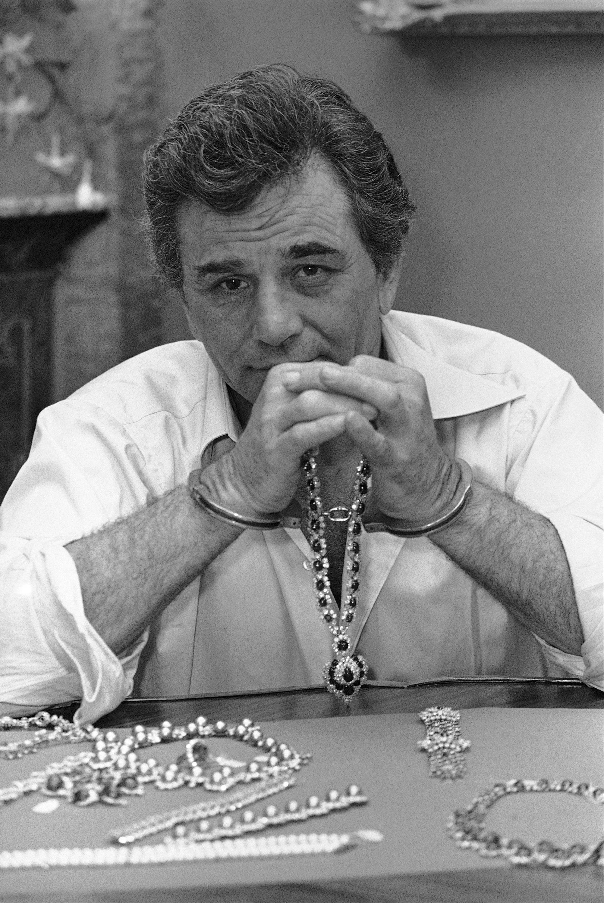 "Actor Peter Falk poses with $8-million in diamonds, emeralds and gold while handcuffed at the set of Columbia Pictures ""Happy New Year"" being filmed in Fort Lauderdale, Fla., on June 3, 1985. The gems were under heavy guard during the shooting session and were reported to have been flown in from New York for the filming. The film also stars Charles Durning, who, with Falk, become jewel thieves."