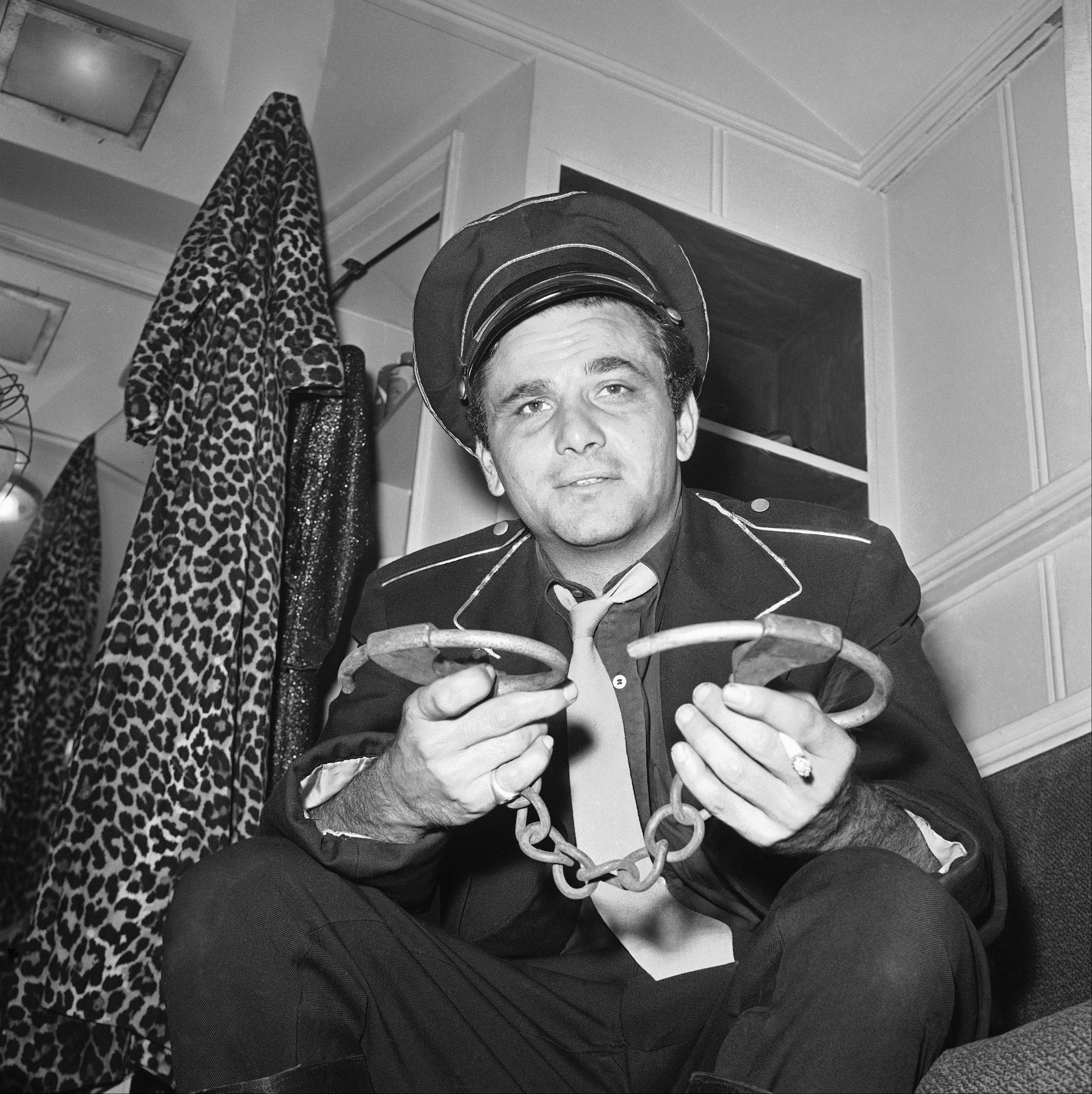"Peter Falk shown December 1962, who stars with Shelley Winters in the film ""The Balcony"" a film in which Winters plays the role of a madam of a brothel and Falk, a chief of police. This type of film known in the industry as a ""Art Film."" Pictures of Peter Falk during acting scene and press interview in which he holds pair of old fashioned handcuffs, he uses in a scene.."