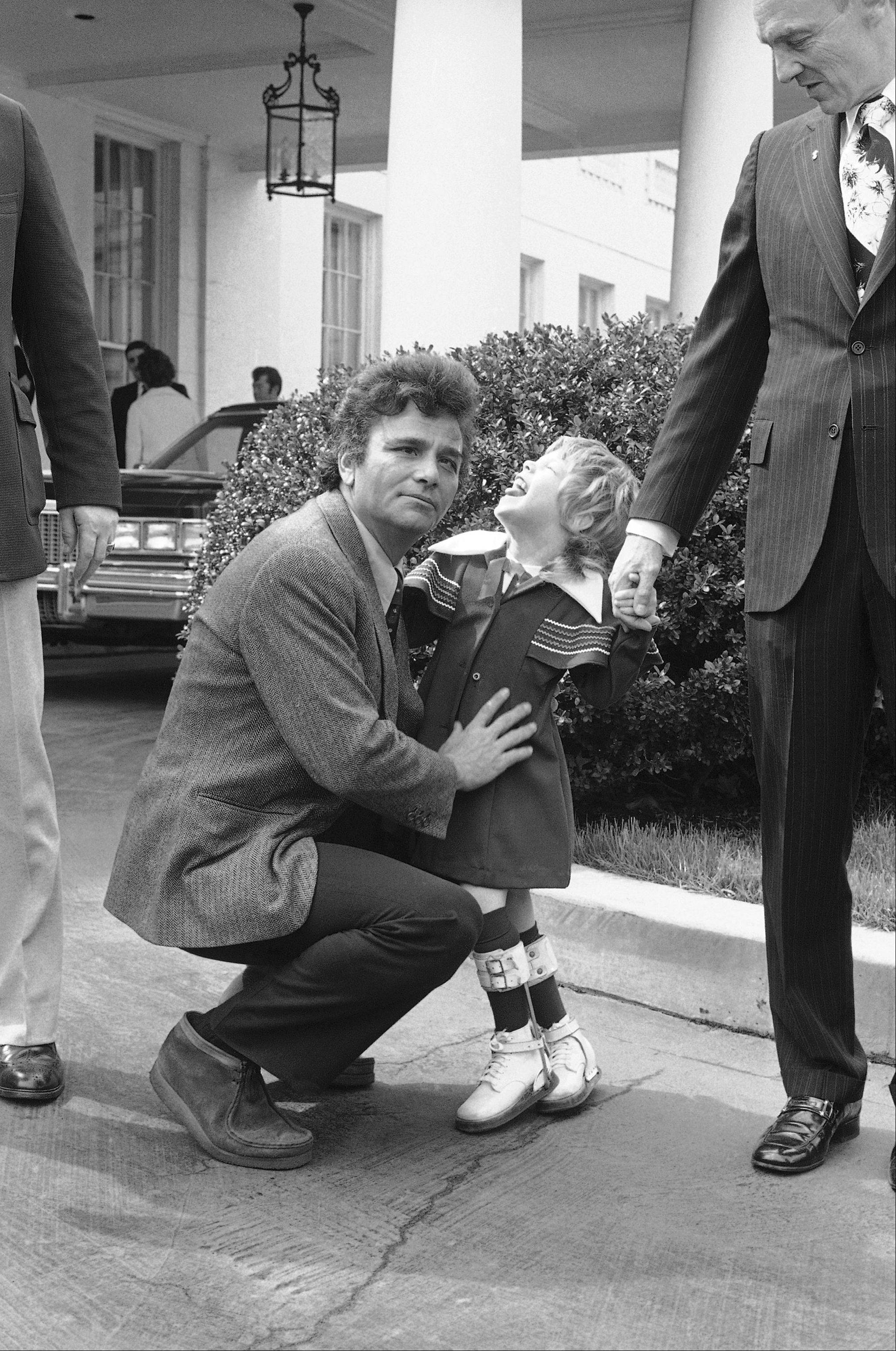 Actor Peter Falk gets a slight rebuff, left, and then permission for a kiss from Pamela Jo Baker, 5, of Wellsburg, W.Va., the 1975 Easter Seal Poster Child, outside the White House on Thursday, March 14, 1975 in Washington after they payed a call as President Gerald Ford.
