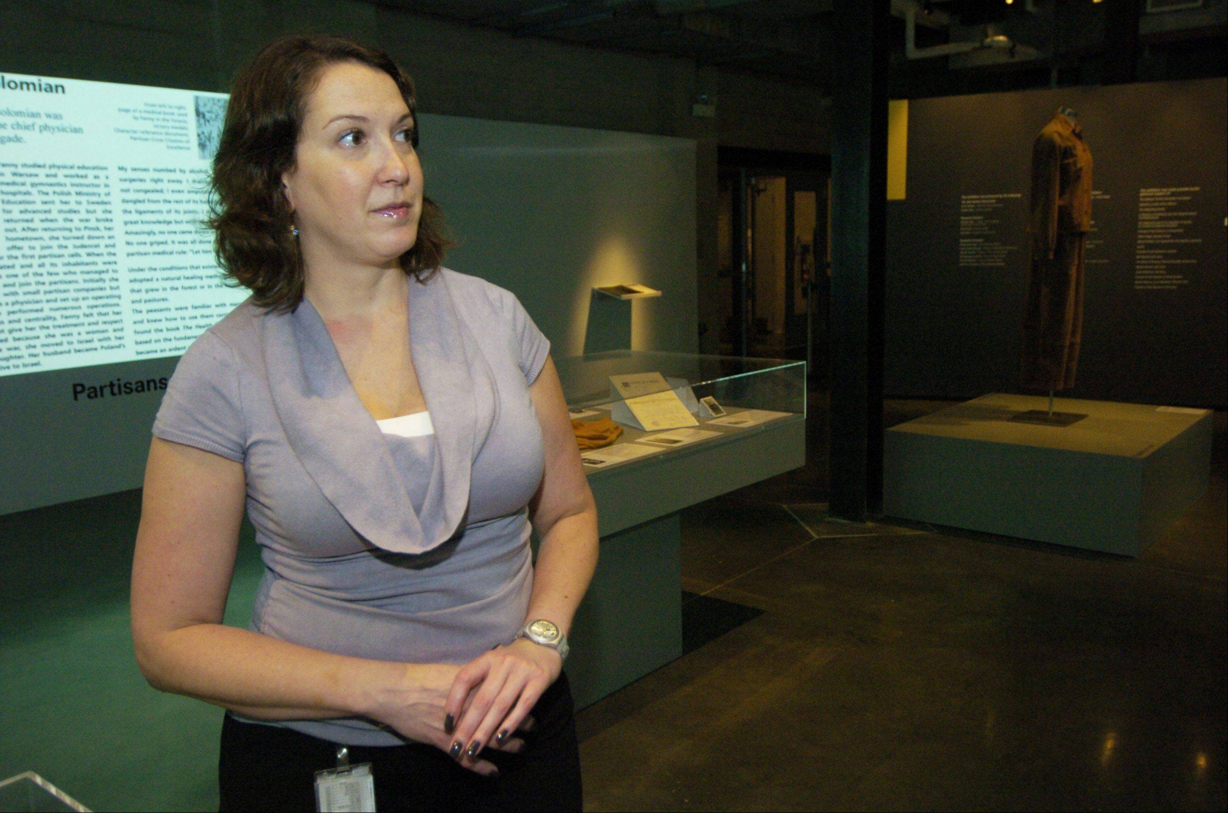 "Arielle Weininger, curator of collections and exhibitions, stands in the ""Women in the Holocaust"" exhibit room at the Illinois Holocaust Museum in Skokie."