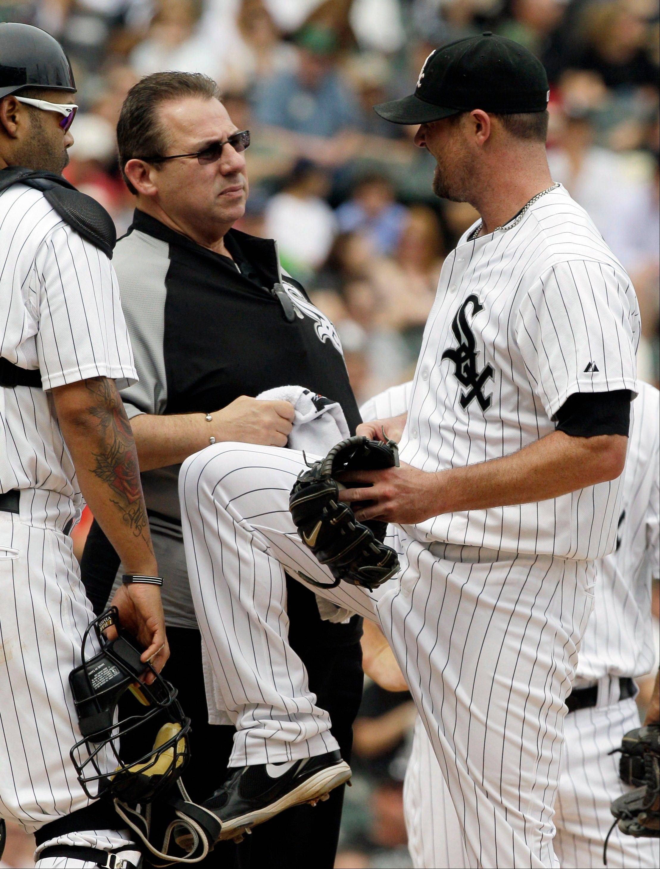 White Sox starter John Danks is checked by a trainer after an injury during the second inning Saturday at U.S. Cellular Field. Danks strained his oblique with two outs in the inning.