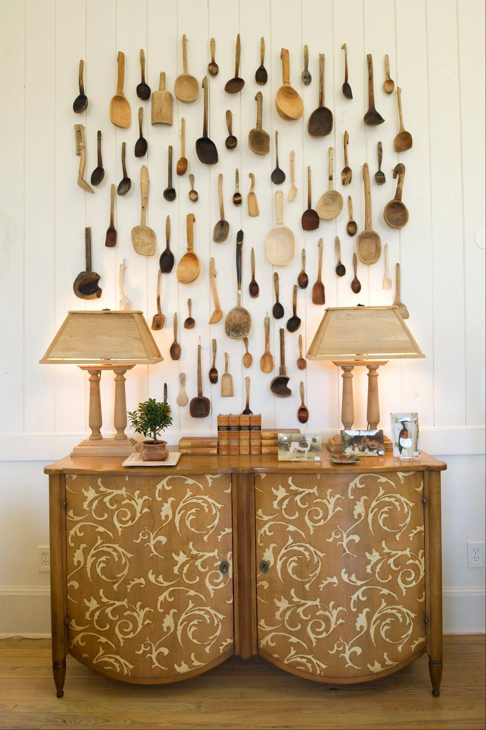 A set of 70 Belgian wooden spoons hangs above a hand-painted French sideboard at Matthews House and Garden in Upperville, Va.