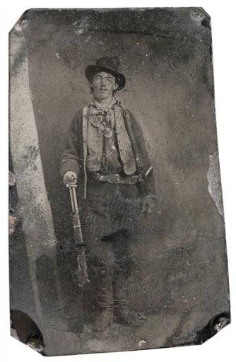 This photograph provided by Old West Show and Auction shows a photograph of a tintype of Billy the Kid taken in 1879 or 1880 in Fort Sumner, N.M. It shows the outlaw standing with his hand resting on a Winchester rifle on one side and a Colt revolver holstered on his right side. The tintype is to be auctioned in Denver on Saturday night and expected to bring between $300,000 to $400,000