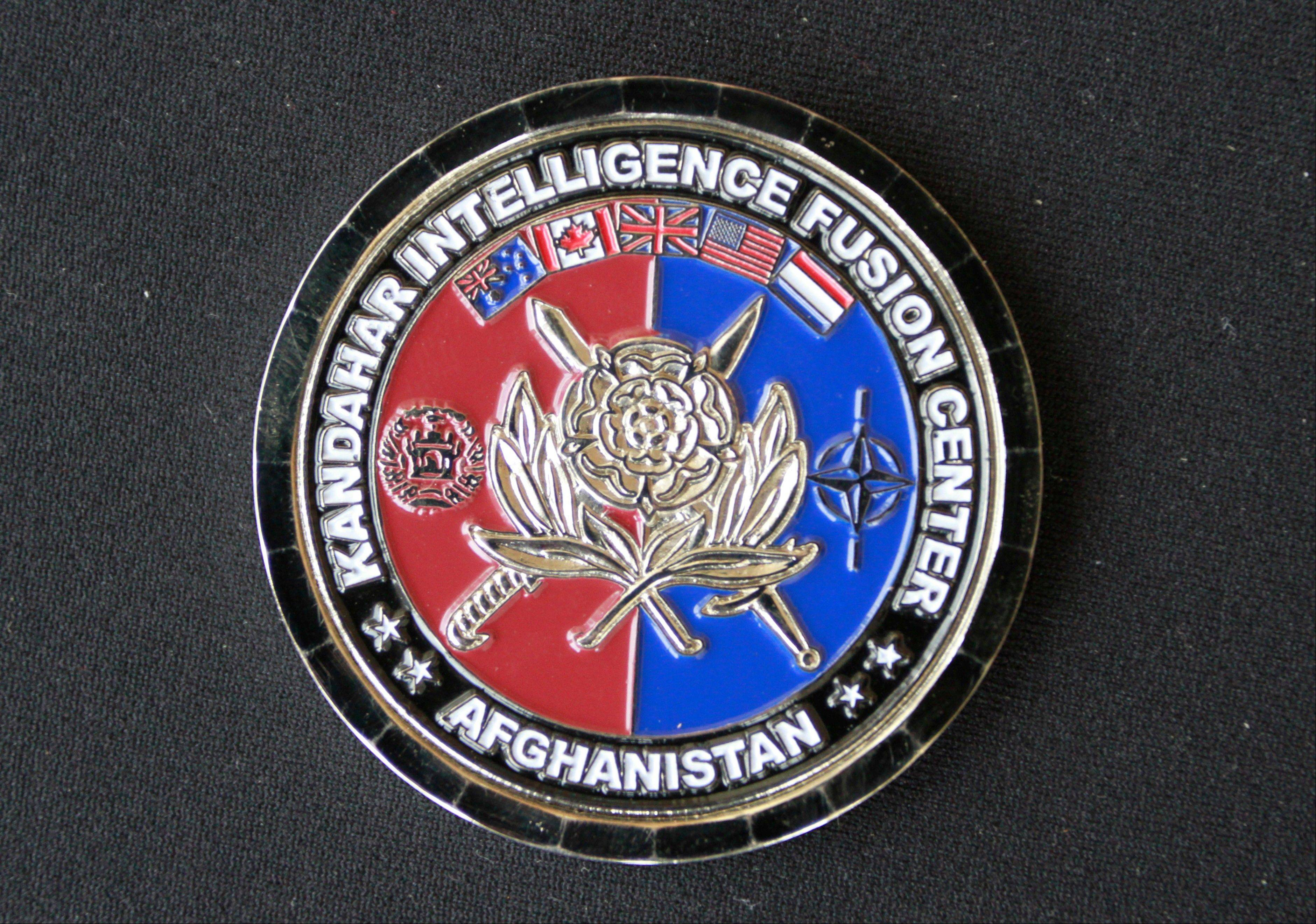 In this March 2011 photo, the front side of a souvenir coin from the U.S. militaryís intelligence center in Kandahar, Afghanistan, is shown, illustrating the shift in focus from helping the population to targeting the enemy. A year ago at this time, military intelligence officers were scrambling to collect and analyze a new form of intelligence _ the social, economic and tribal ins and outs of each valley and hamlet seen as crucial to helping commanders tell the good guys from the bad guys, learn what local Afghans really needed from their government and undermine the Taliban-led insurgency by gradually winning hearts and minds.