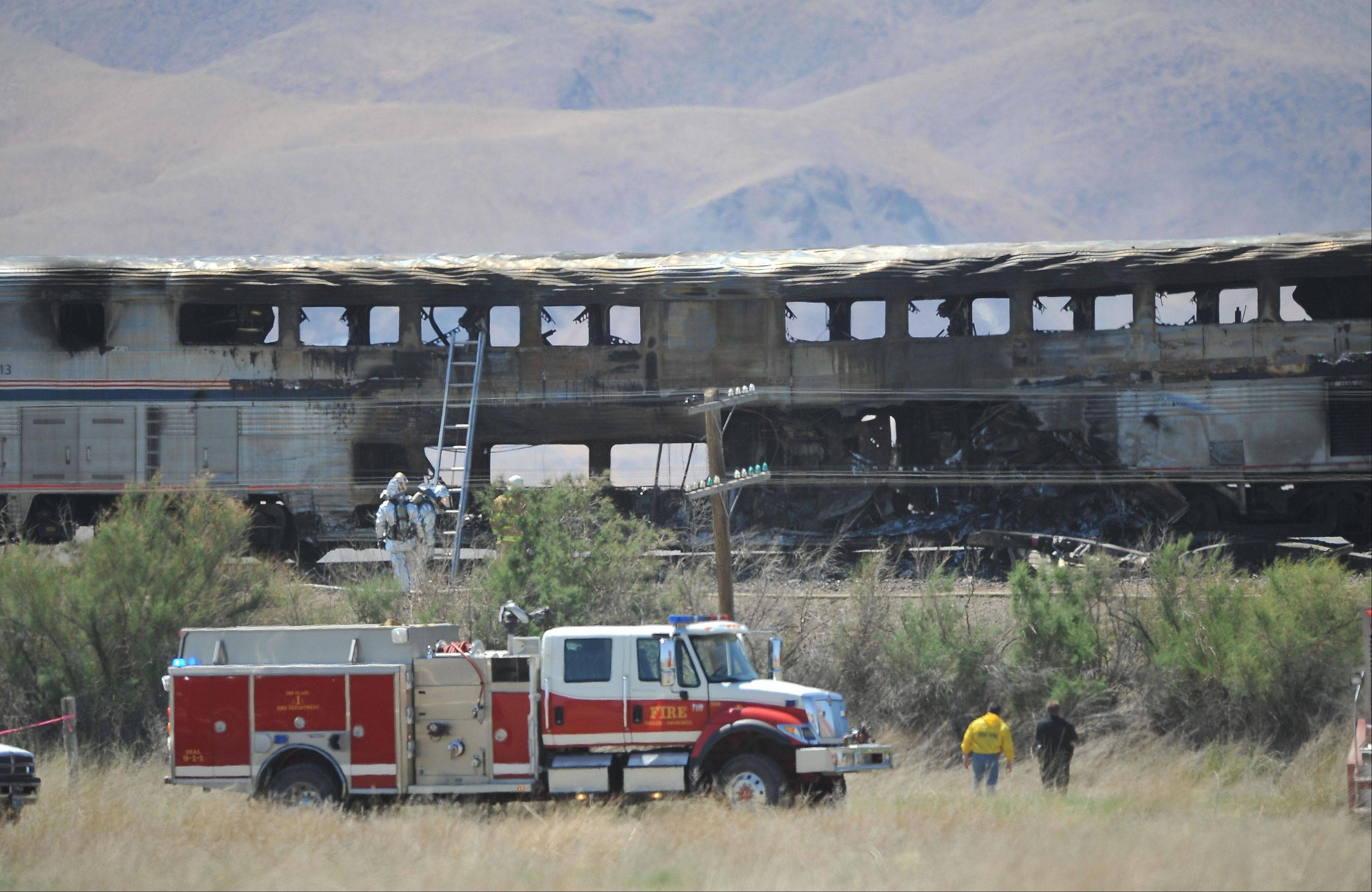 Amtrak passenger cars sit still smoldering after the train was struck by a semi truck on US 95 north of Fallon, Nev., Friday June 24, 2011. The driver of the truck and a passenger were killed, and officials must let the wreck cool off before they continue their search.