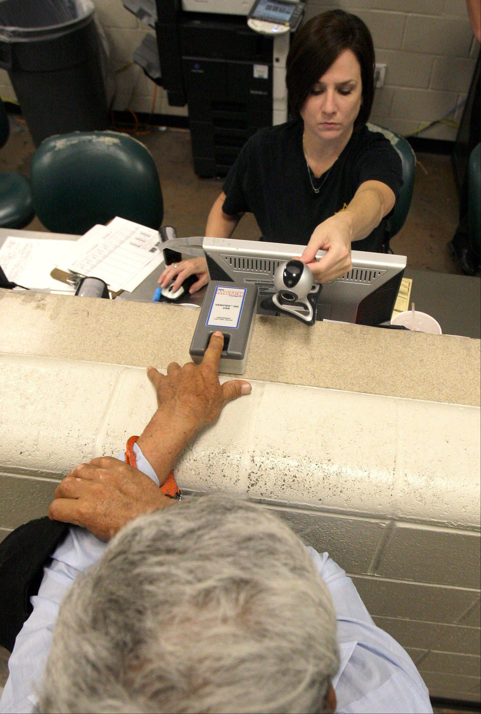 A suspect, bottom, is photographed and checked for his immigration status with a fingerprint scanner by a Maricopa County sheriff's detention officer last year in Phoenix.