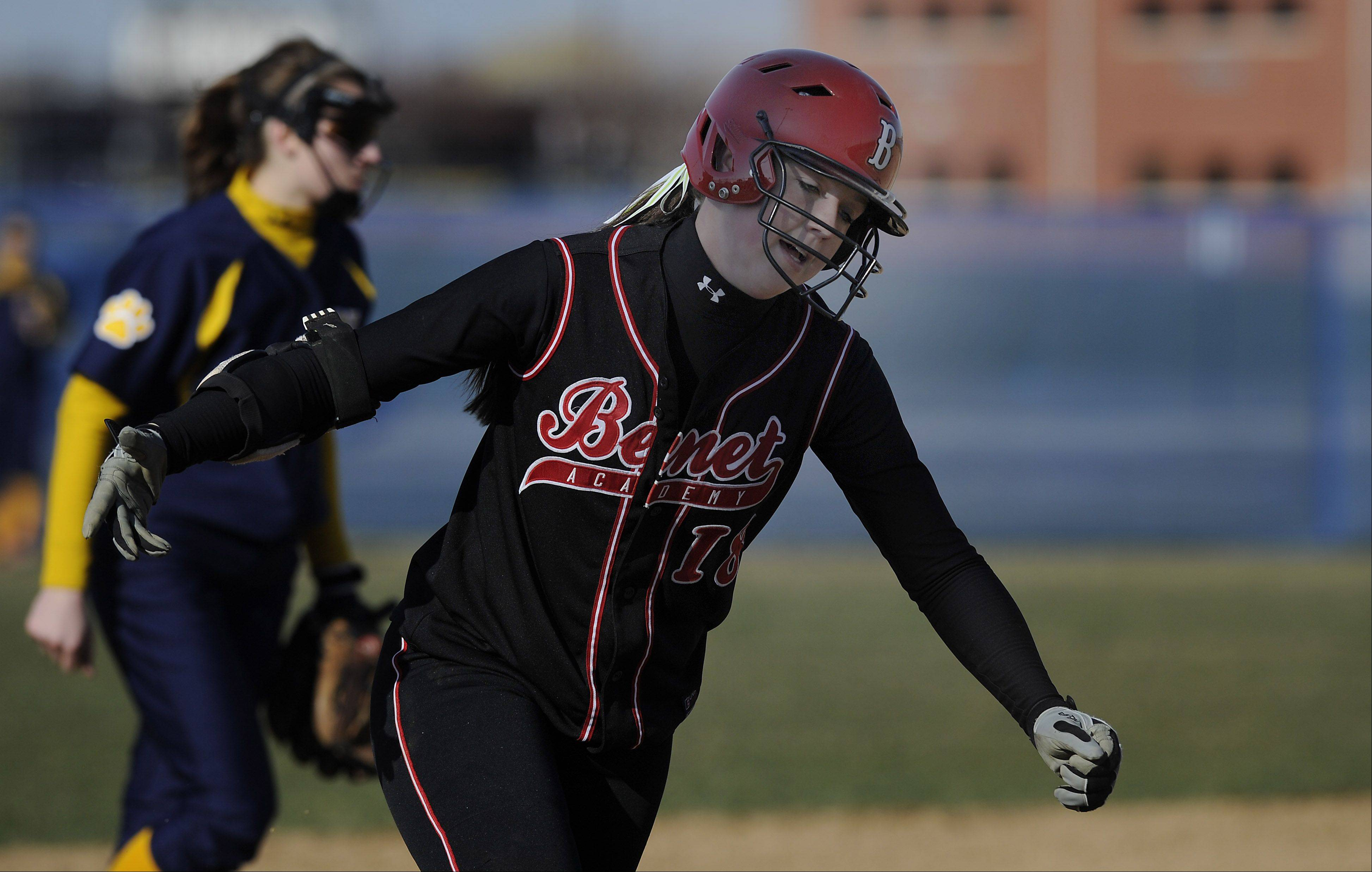Benet Academy's Maeve McGuire rounds third base heading for home after she plaster one over the left-center field fence for a second inning grand slam in the girls softball game against Neuqua Valley High School on Monday.