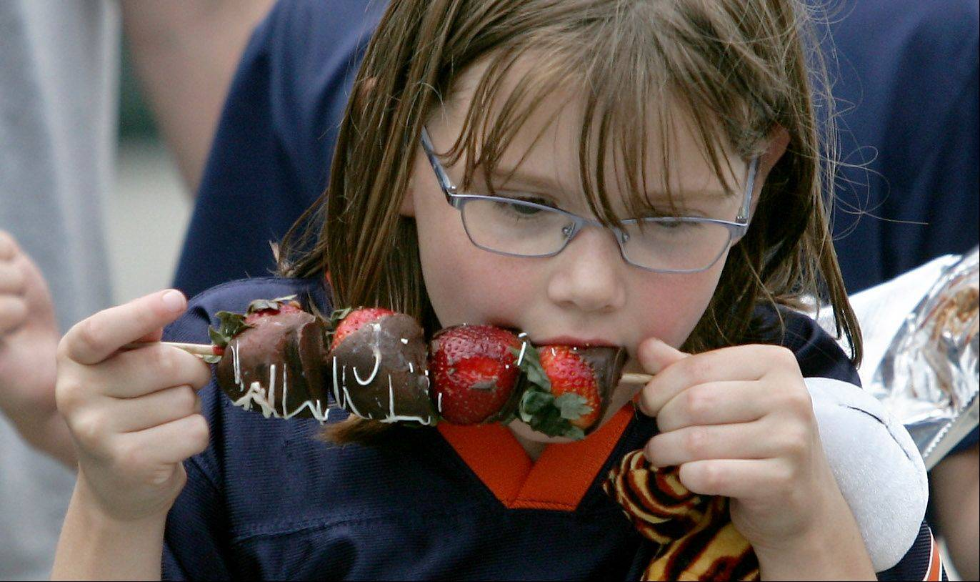 Monyca Grimmer, 7, of Des Plaines enjoys a chocolate-covered strawberry kebab from the Strawberry Patch during the 2010 Taste of Des Plaines, which turned out to be the last one.