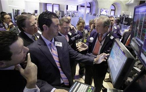 In this June 22, 2011 photo, traders gather at the post of specialist Stephen D'Agostino, foreground second left, on the floor of the New York Stock Exchange. World markets were mixed Monday, June 27, as Greece's parliament began debating harsh new austerity measures that must pass for the country get its next batch of emergency financial aid.