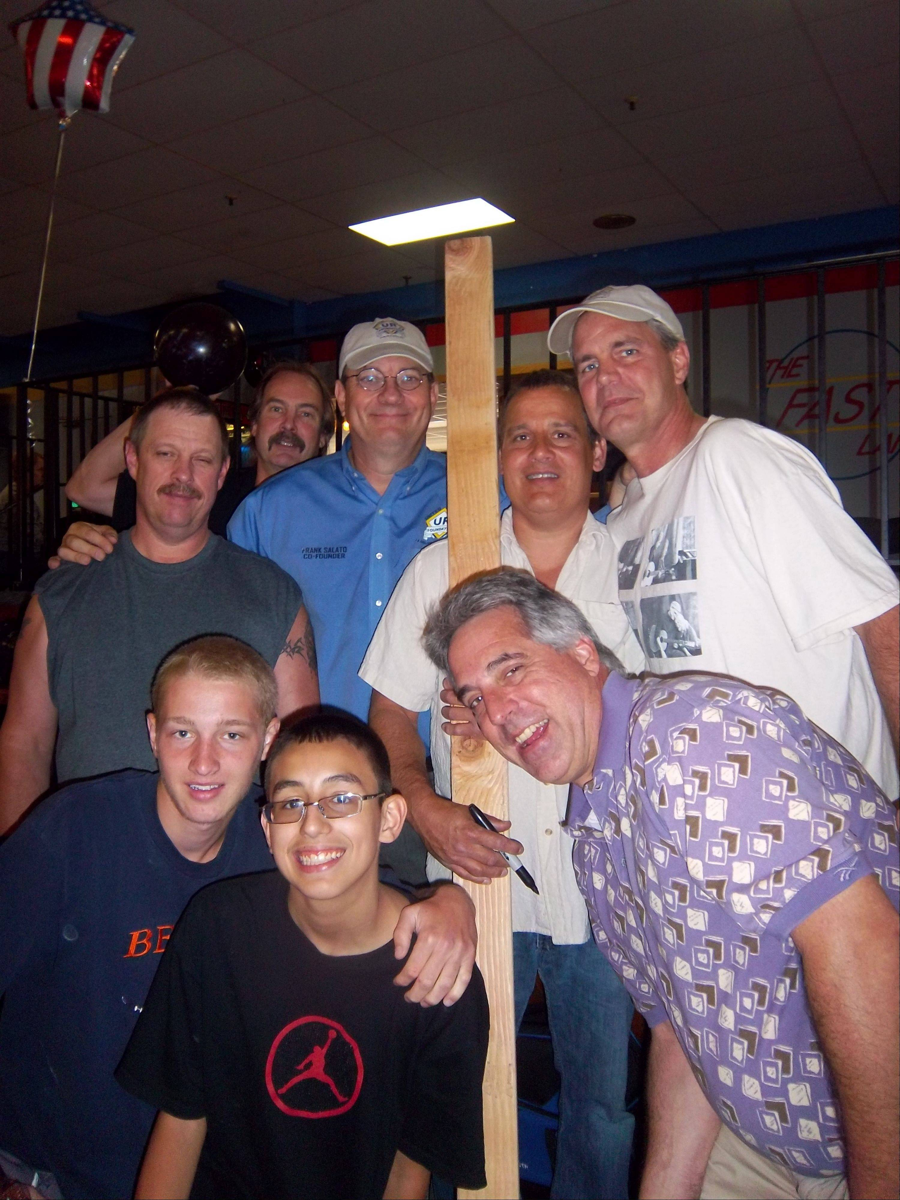 Greg Andejeski, (back left), and his brother Gerry Andejeski, (holding board), take a moment for a snapshot with some of their family and friends. United Relief Foundation co-founder/president Frank Salato is left of Gerry and United Relief Foundation Director Steve Alma is on right.