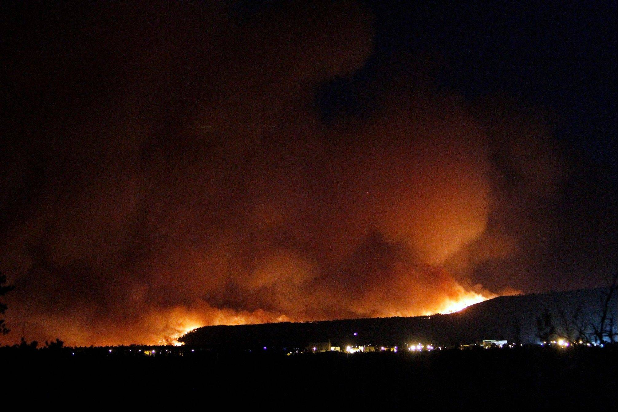 A wildfire crests over the hills above Los Alamos National Labs Sunday night. The fast-moving wildfire forced officials at the Los Alamos National Laboratory to close the site Monday.