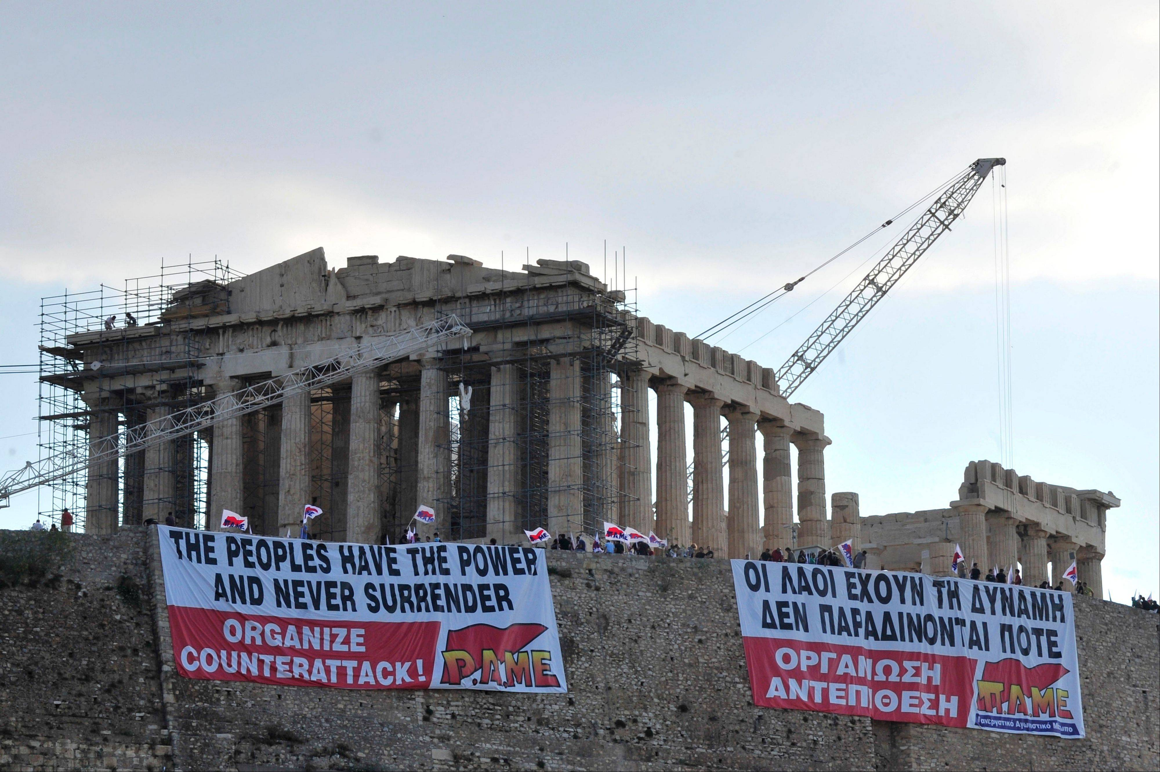 Protesters of a Communist Party-backed union, PAME, hang banners in English and Greek reading: �The peoples have the power and never surrender. Organize counterattack� in front of the Parthenon temple on the Acropolis hill in Athens Monday.