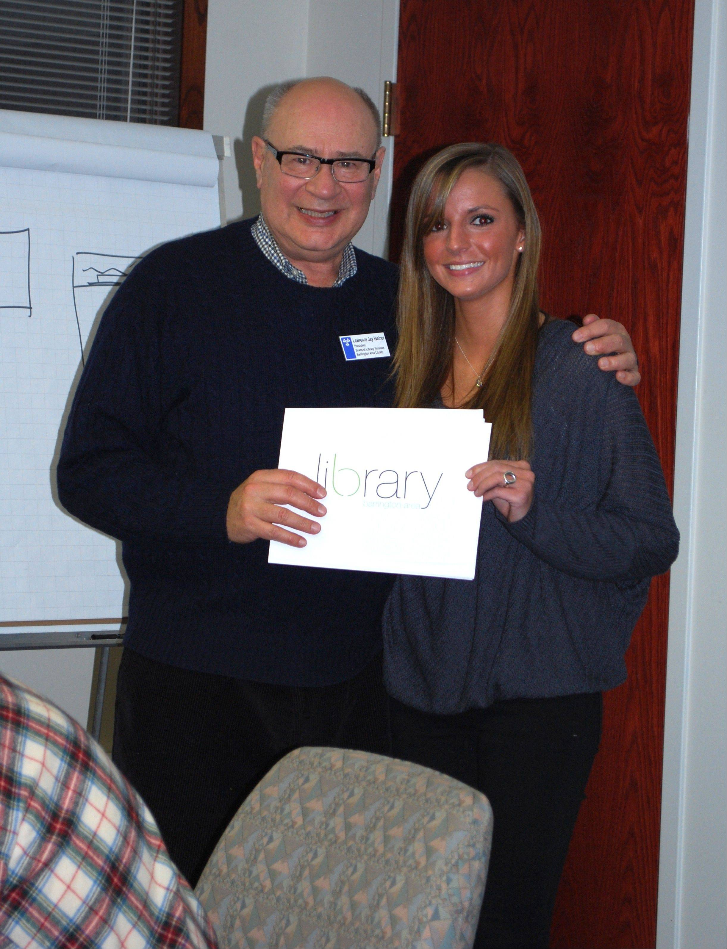 Former Library board of trustees President Lawrence J. Weiner congratulates Kasey Dasko on her winning logo.