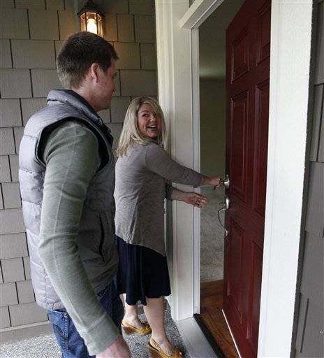 In this June 24, 2011 photo, Laura Young, 28, left and her husband Andre Gjerde, 30, open the front door of their new home moments after receiving the keys to it, in Bothell, Wash. The bottom has fallen out of home prices in several markets around the country. That may be great news for bargain hunters, but it means that all homebuyers need to proceed with caution.