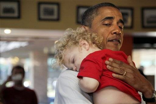 President Barack Obama holds a sleeping baby boy as he visits Ross' restaurant in Bettendorf, Iowa, Tuesday, June 28, 2011.