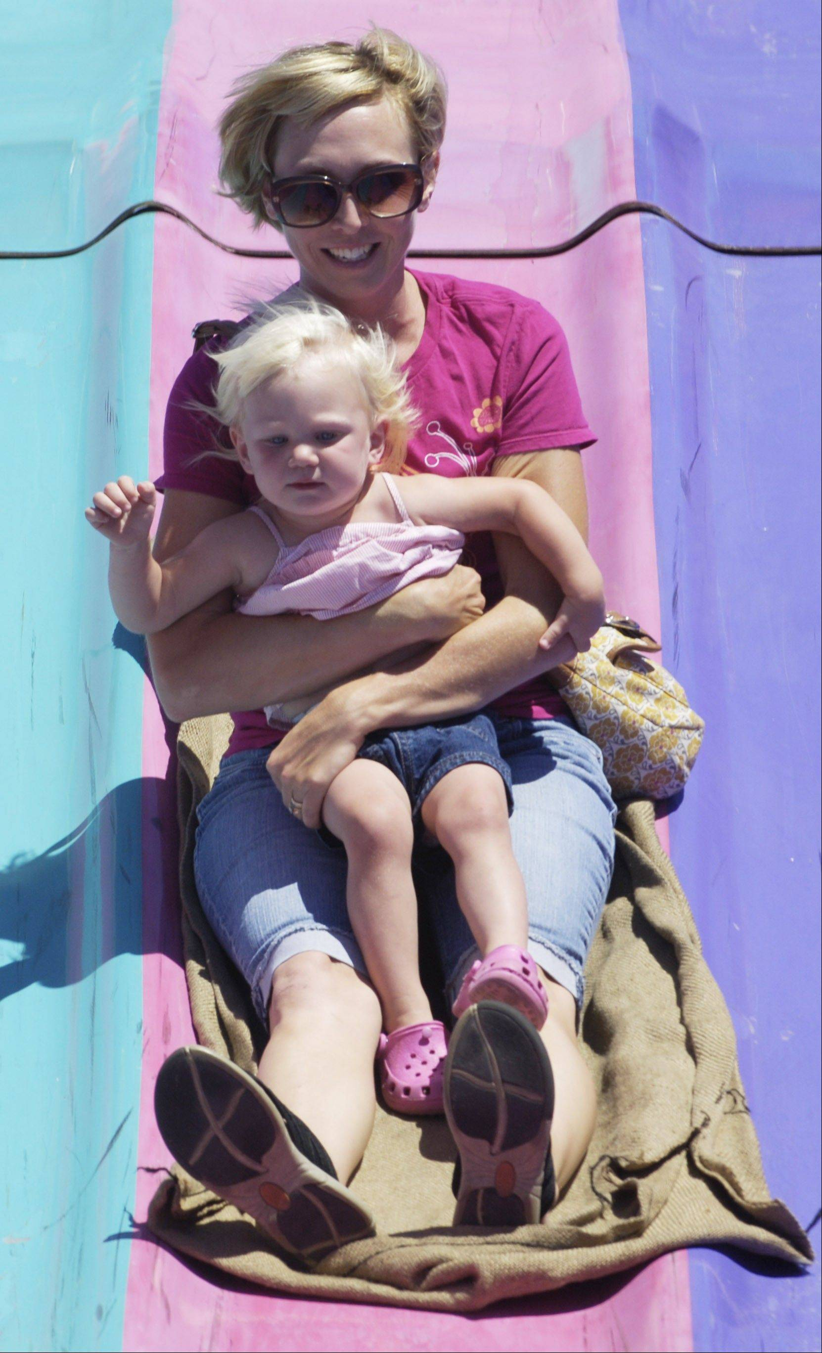 Holly Carey of Elgin and her daughter, Olivia, 2, go down the Fun Slide at Bartlett's Fourth of July fest in 2010.