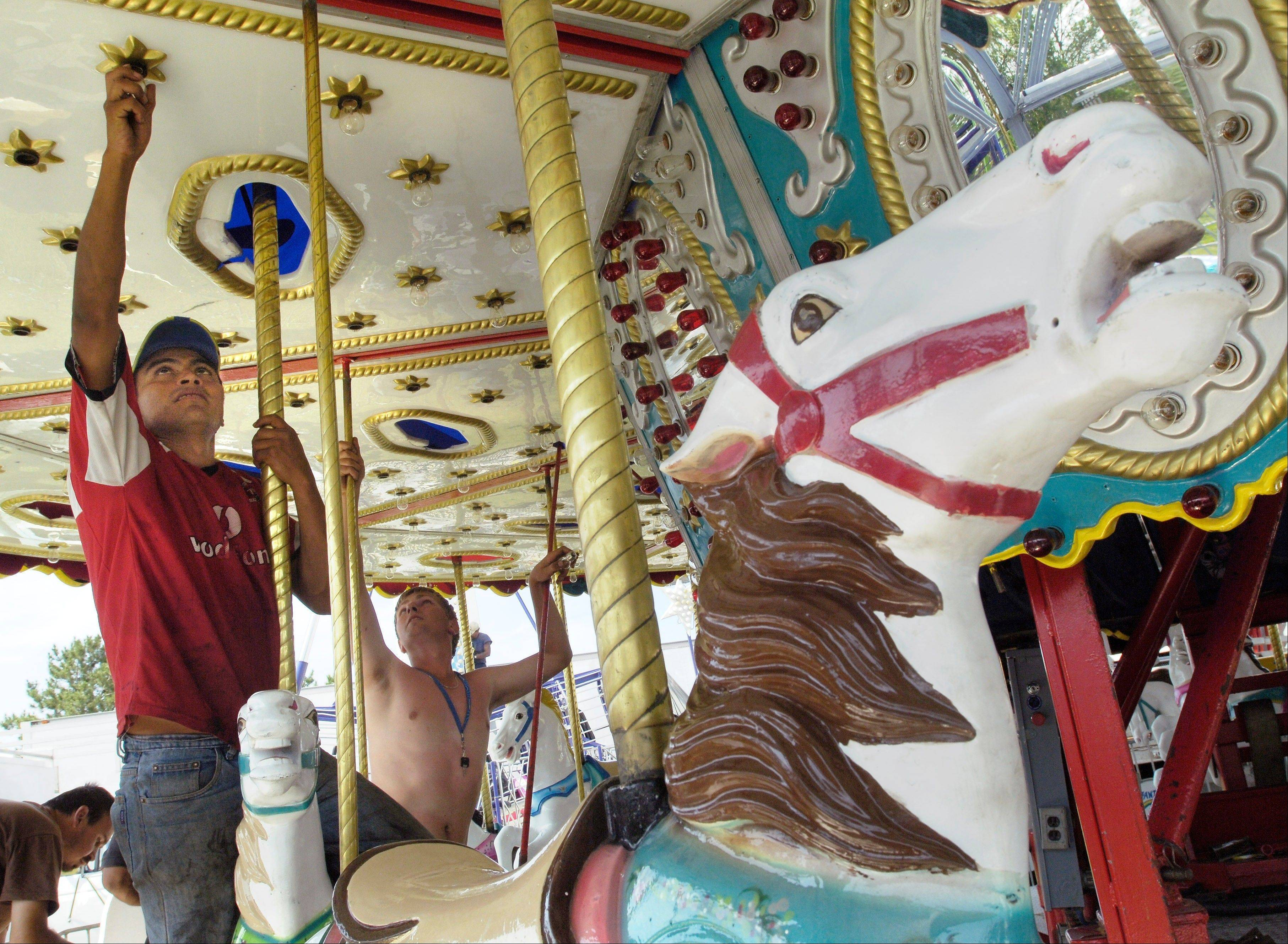 The finishing touches are put on the carousel at the Mount Prospect festival in Melas Park.