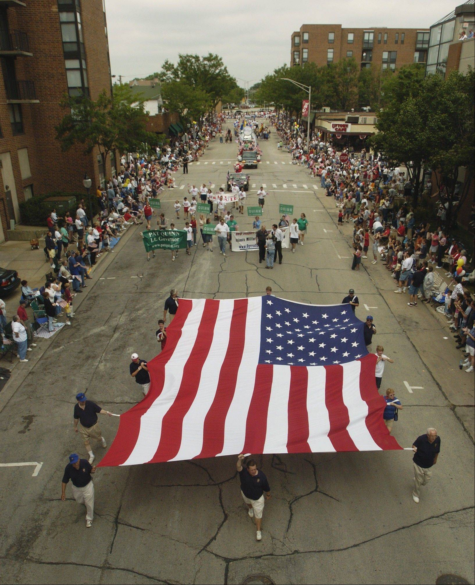 the Lions Club of Arlington Heights marches in a Fourth of July parade with a huge American Flag.