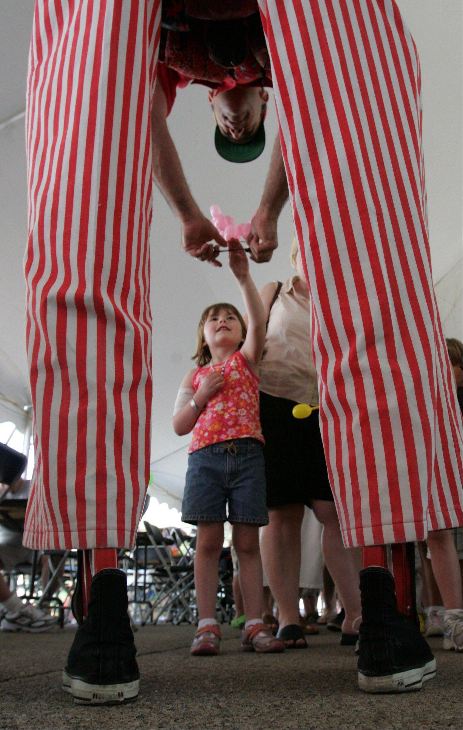 Frank Birdsall, who returns to the Barrington festival this year, gives a child a balloon at a recent year's fest.