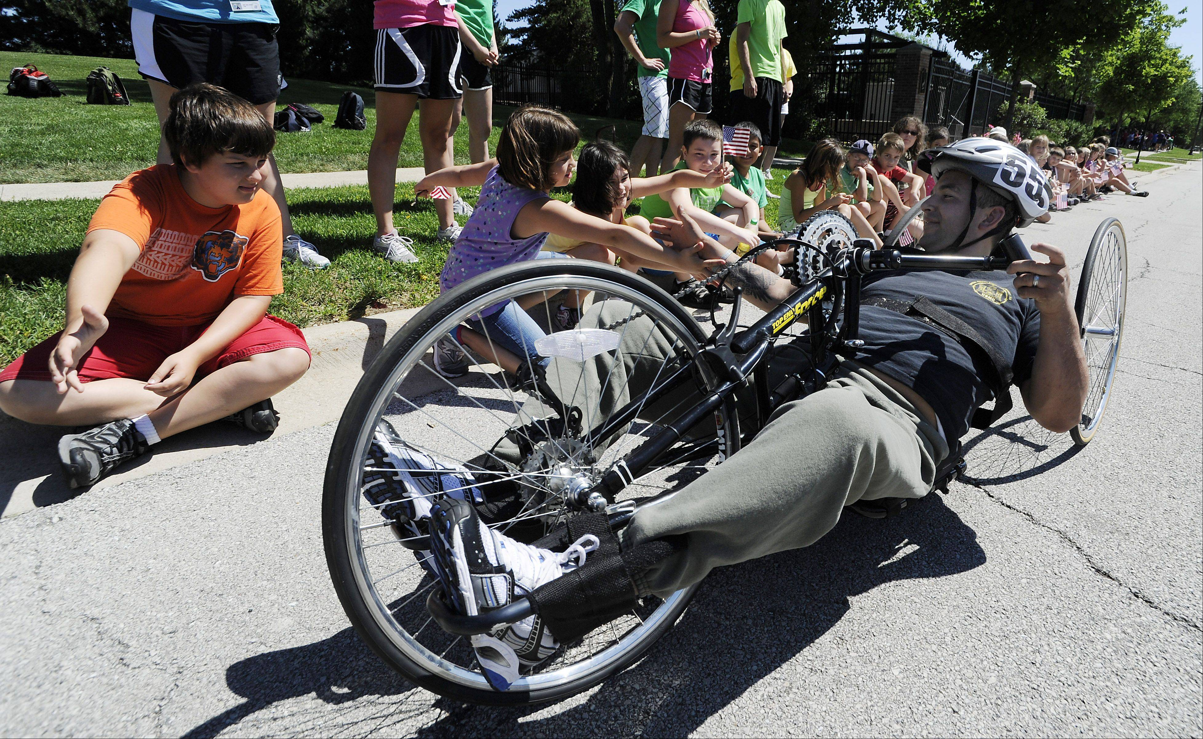 Alberto Velasco, 31, of Schaumburg, one of the athletes participating in the handcycle race in the upcoming Tour of Elk Grove, gets a start in the mini-race with high-fives from the kids at the Elk Grove Village summer camp Voyager on Tuesday.