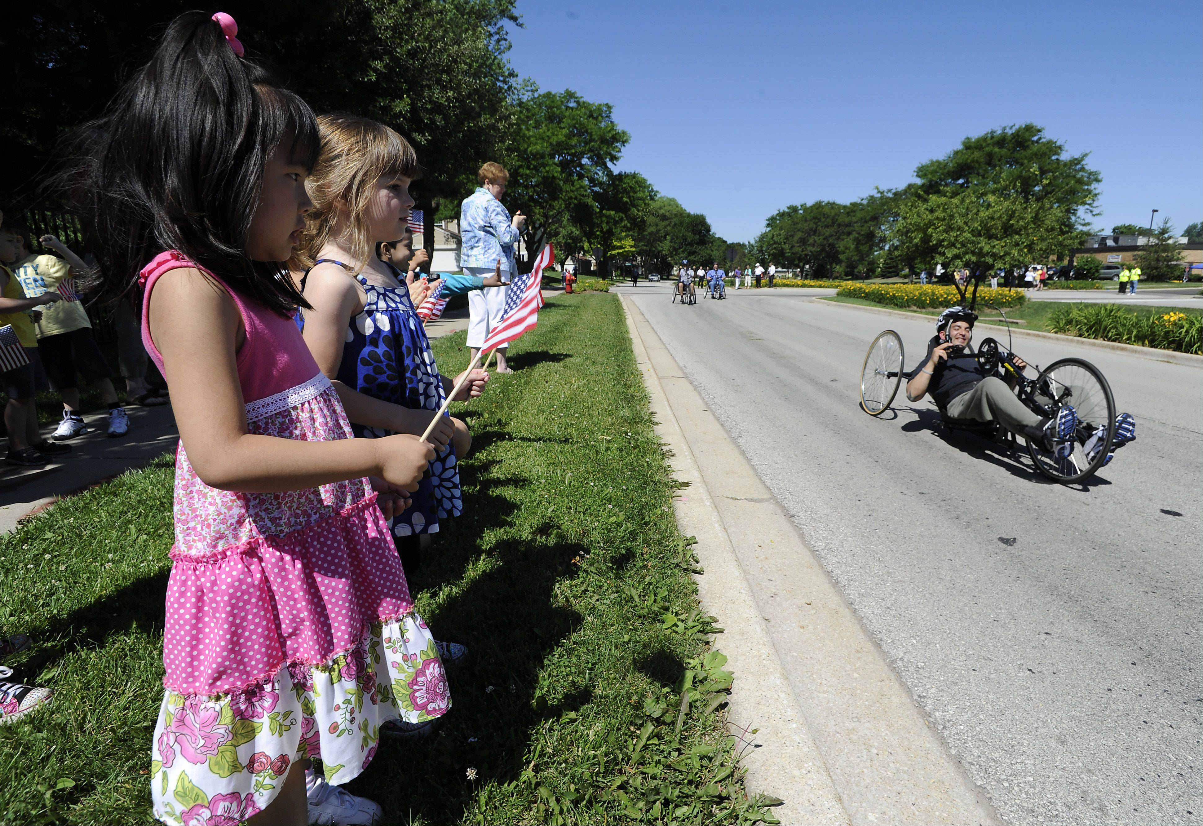 Alberto Velasco, 31, of Schaumburg, one of the athletes that will participate in the handcycle race in the upcoming Tour of Elk Grove, gets a start in the mini-race with cheers from Rinka Yamakawa, 5, and Madeline Aldrich, 4, of an Elk Grove Village Park District preschool camp.