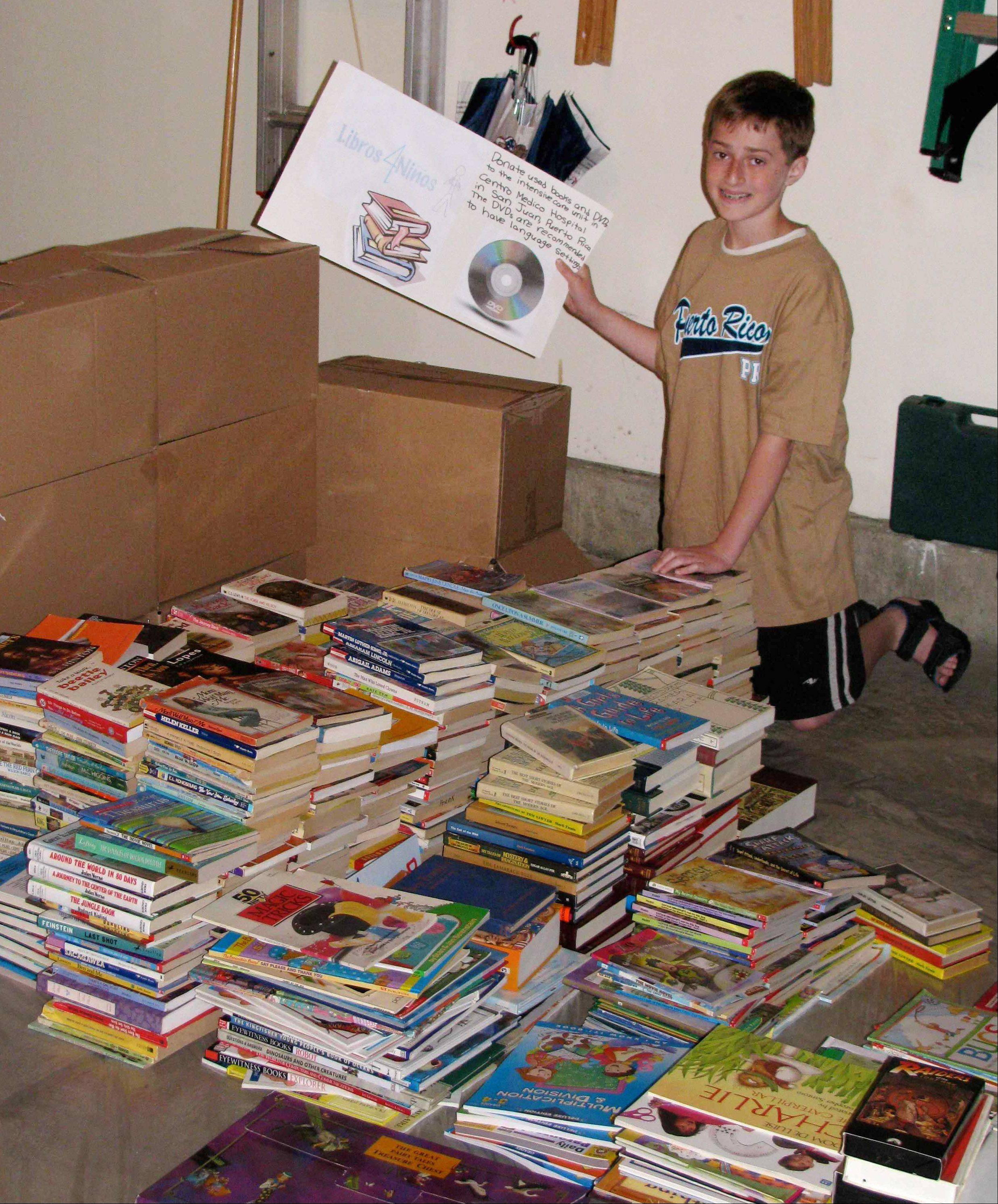 Stephen Cohn with some of the books he and classmates collected to donate to the hospital in Puerto Rico where he was treated for bleeding ulcers during spring break.