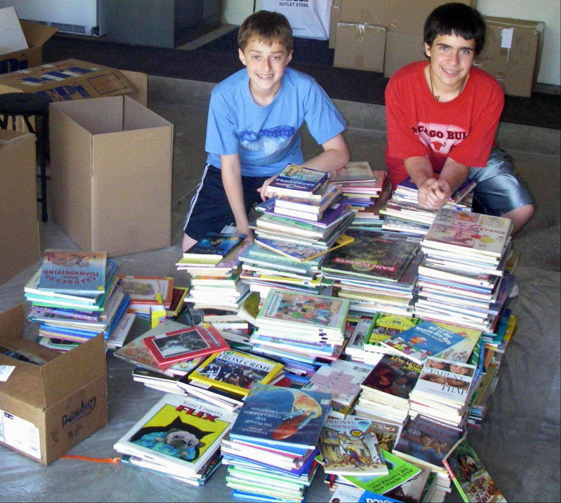 Stephen Cohn, left, and his friend Daniel Mortge with the books and DVDs they received from classmates. In all, they collected more than 1,500 items to be donated.