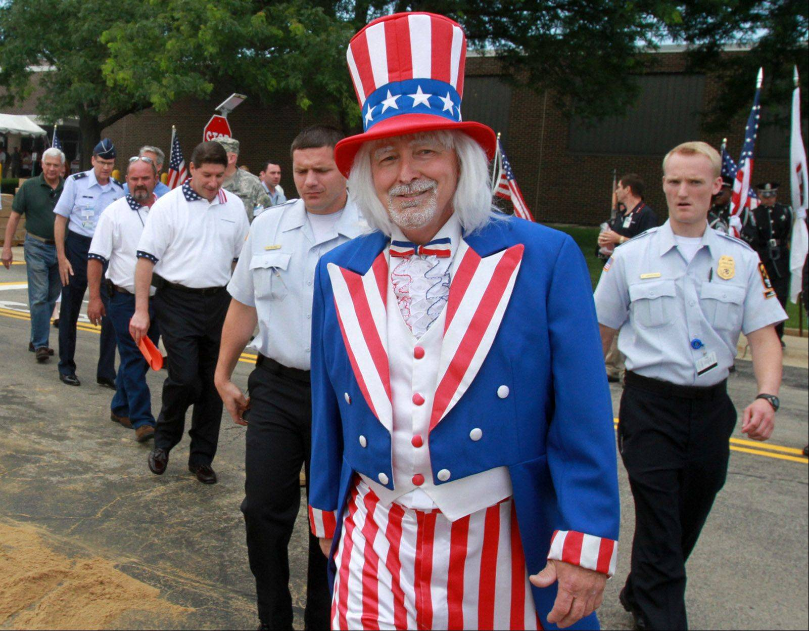 Joe Boshold, a manager at Northrop Grumman Corp., leads a parade of dignitaries as Uncle Sam to kick off festivities at the 20th annual America Day at the global security company�s Rolling Meadows campus.