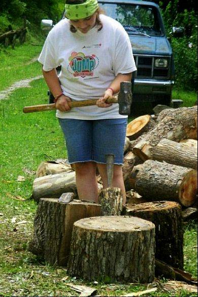 Gwen Moser, a member of the Antioch church group heading to Haiti on Saturday, chops wood at the home of an elderly couple during the Red Bird Mission in Southeastern Kentucky last year.