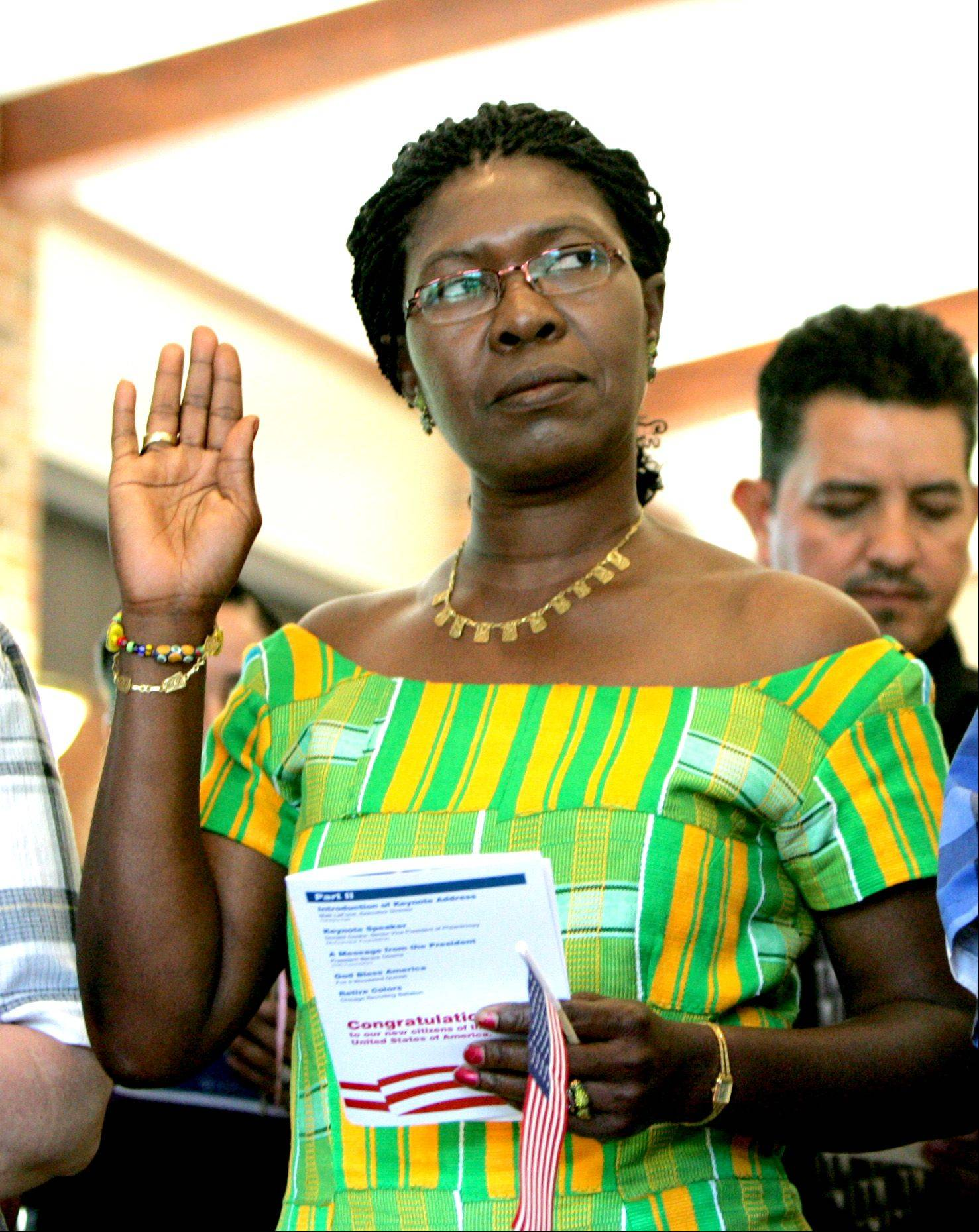 Augusta Kportufe, originally from Ghana, takes her oath of allegiance Thursday during a citizenship ceremony at Cantigny Park in Wheaton. A total of 94 people from 34 countries became U.S. citizens.