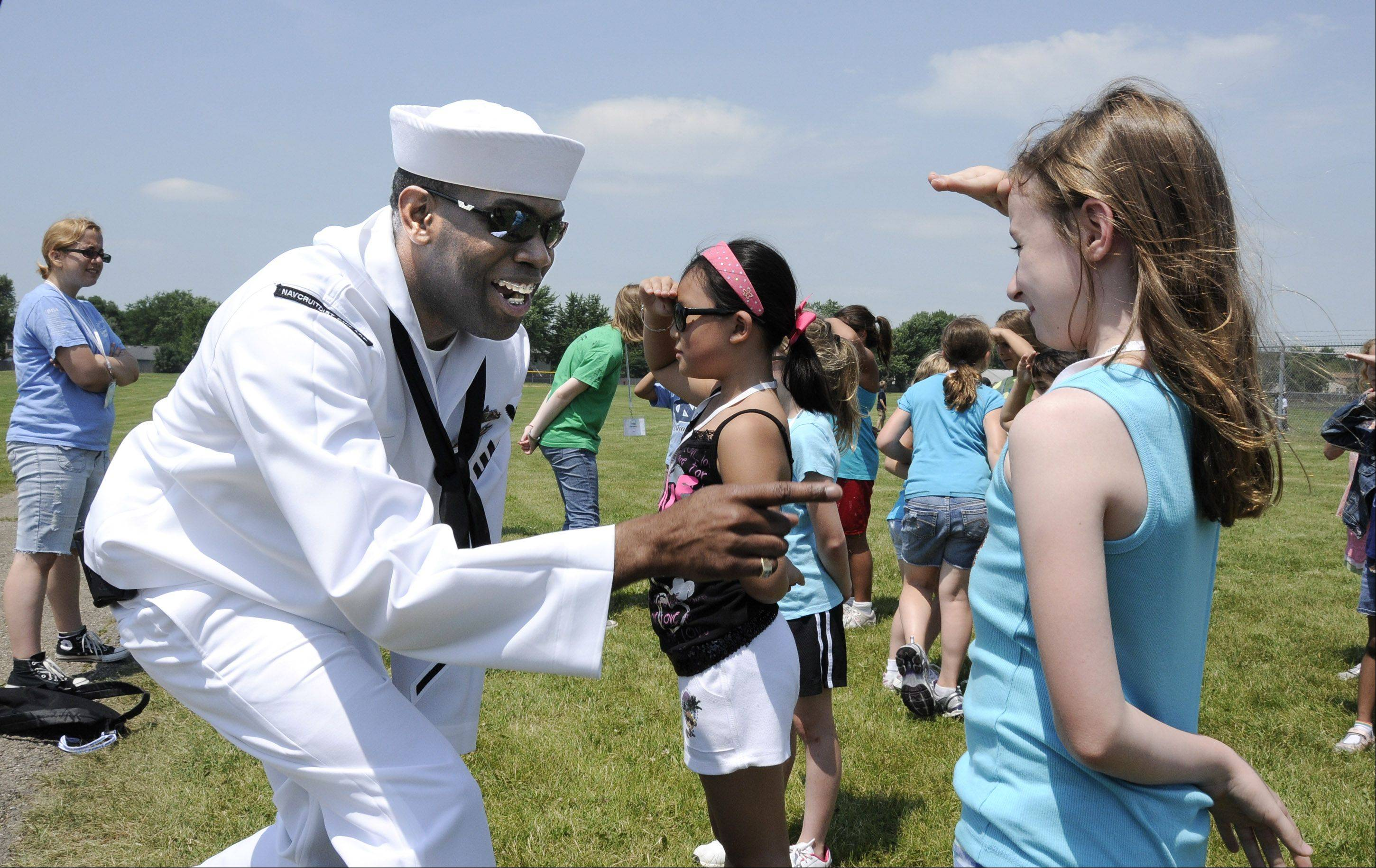 Recruiter Demetrius Lash tries to get Paige Breslin to laugh while she stands for inspection. Personnel from the Navy visited the summer camp Thursday at the Illinois Mathematics and Science Academy in Aurora to talk about the Navy and have fun with the kids.