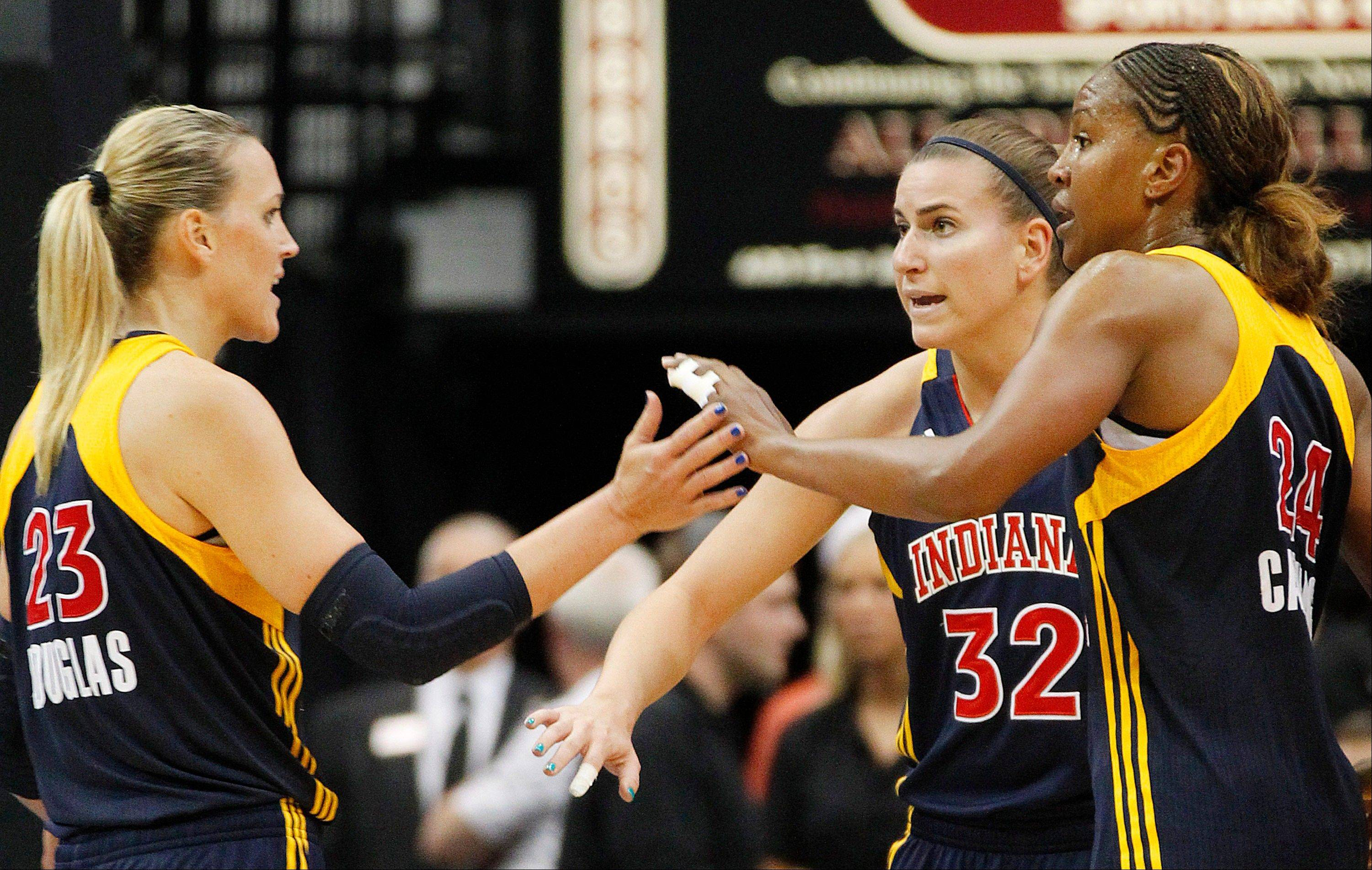 Indiana Fever forward Katie Douglas, left, is congratulated by teammates Jeanette Pohlen (32) and Tamika Catchings in a recent game against the Minnesota Lynx. Catchings is the leading vote-getter for the WNBA All-Star Game.