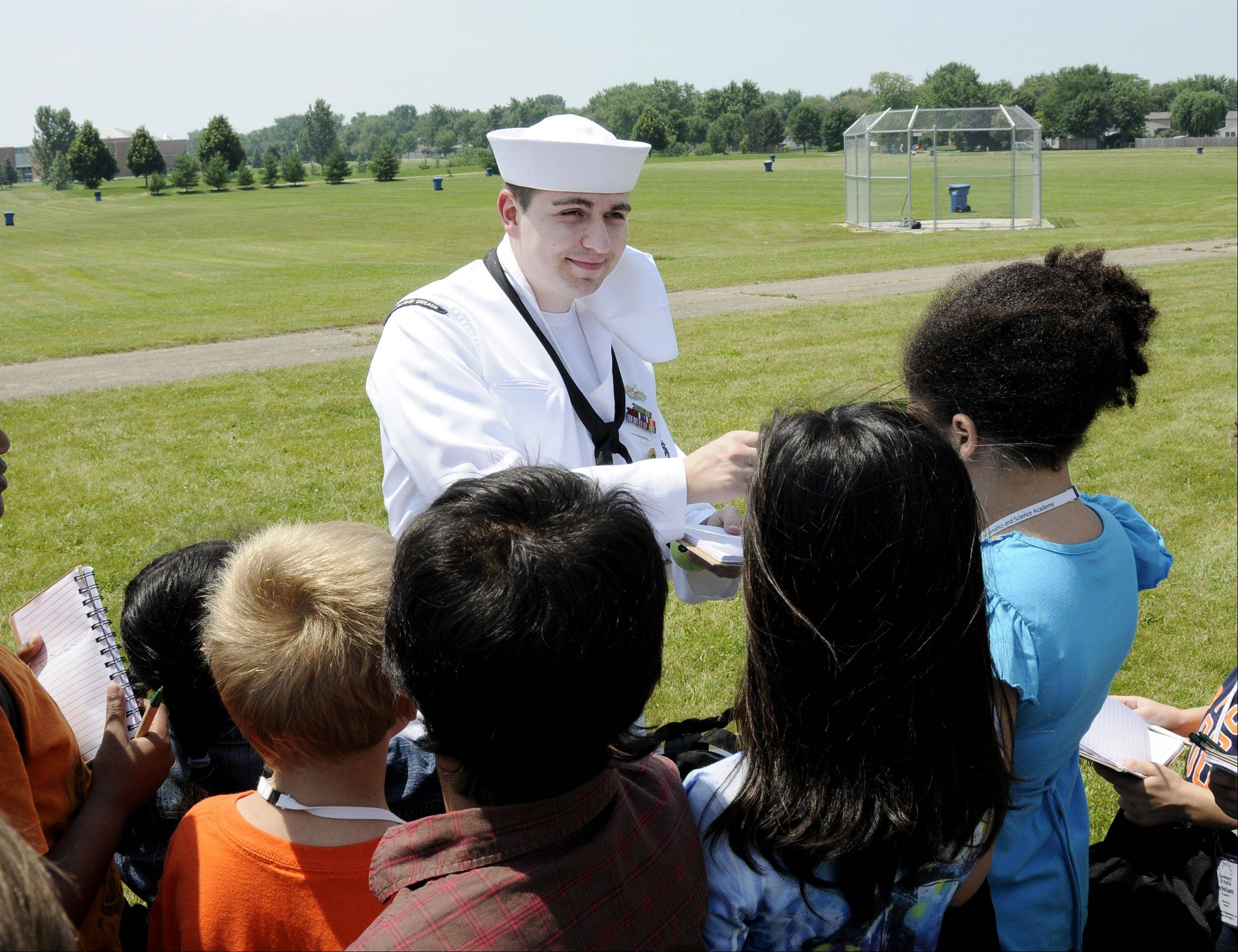 Navy personnel, including recruiter Raul Mot, visited the summer camp at IMSA in Aurora Thursday to talk about the Navy, sign autographs, and have fun with the kids.