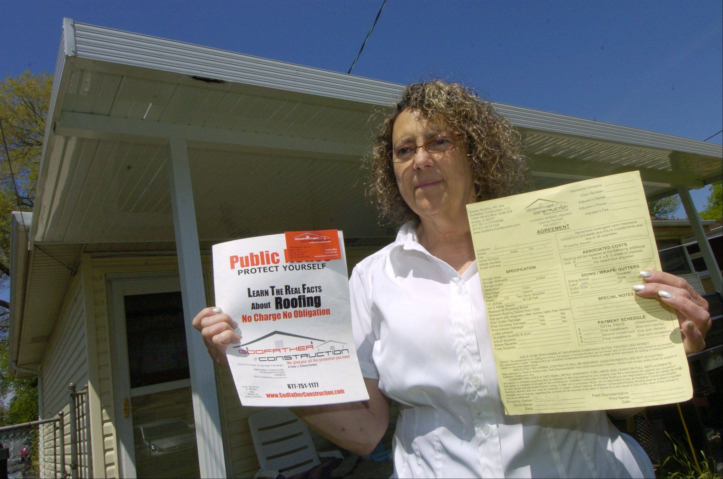 Susan Czach of Des Plaines holds up a brochure, left, from Godfather Construction warning people about storm chasers, fly-by-night companies that move into storm-damaged areas, which, ironically, is exactly what they are accused of doing. At right is her contract with the company.