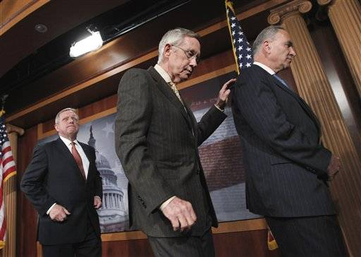 Having insisted there is too much to do for lawmakers to spend a week away from the Capitol, Senate Majority Leader Harry Reid of Nev., center, walks with Senate Majority Whip Richard Durbin and Sen. Charles Schumer, D-N.Y