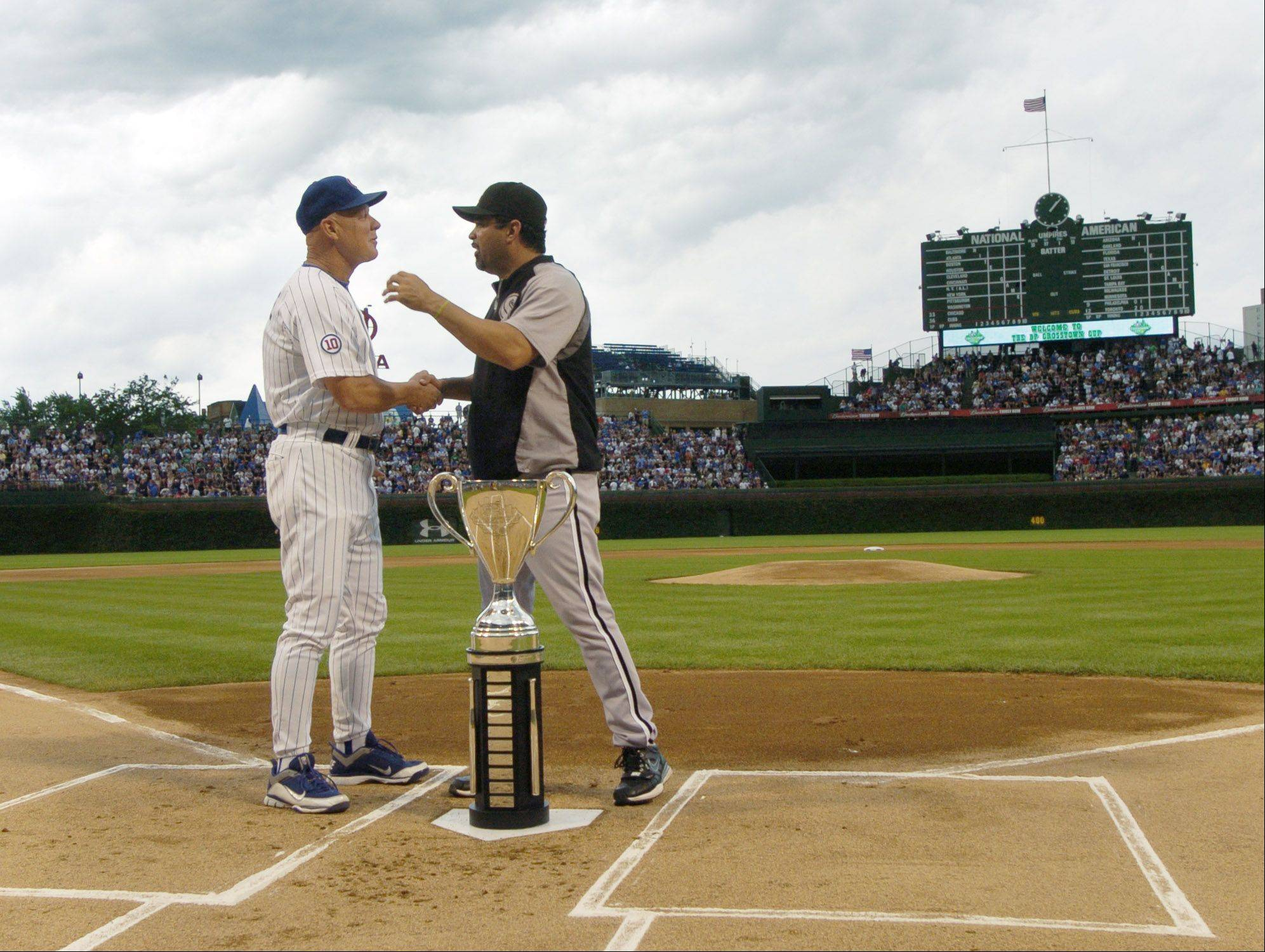 Cubs manager Mike Quade and Sox manager Ozzie Guillen chat while the Crosstown Cup rests on home plate before Friday's game at Wrigley Field.