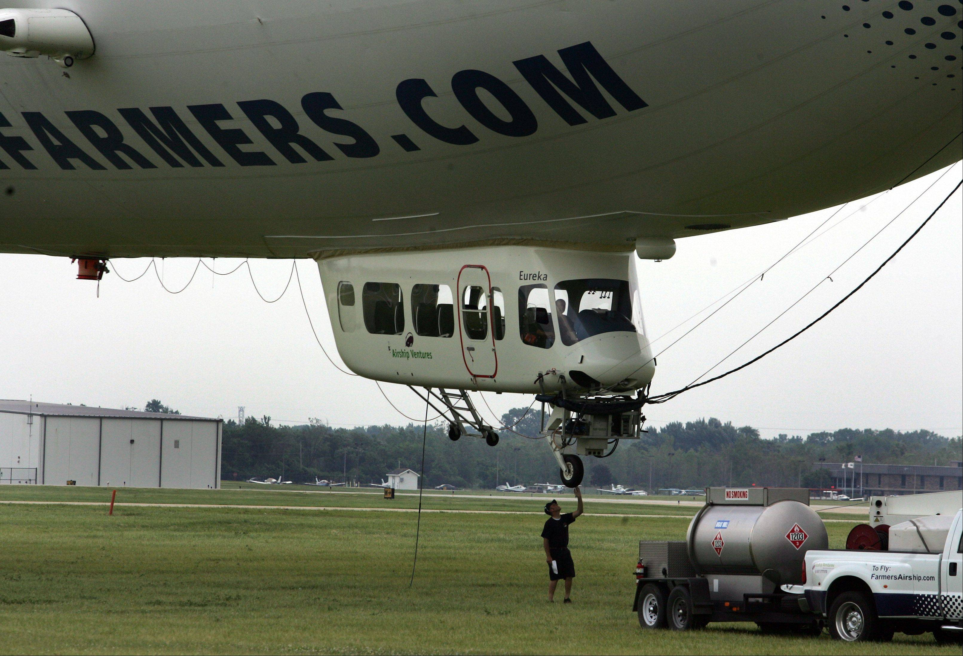 A crew member performs a check on the Farmers Airship, one of only two Zeppelins currently flying globally, as it makes a stop at the DuPage County Airport in West Chicago.