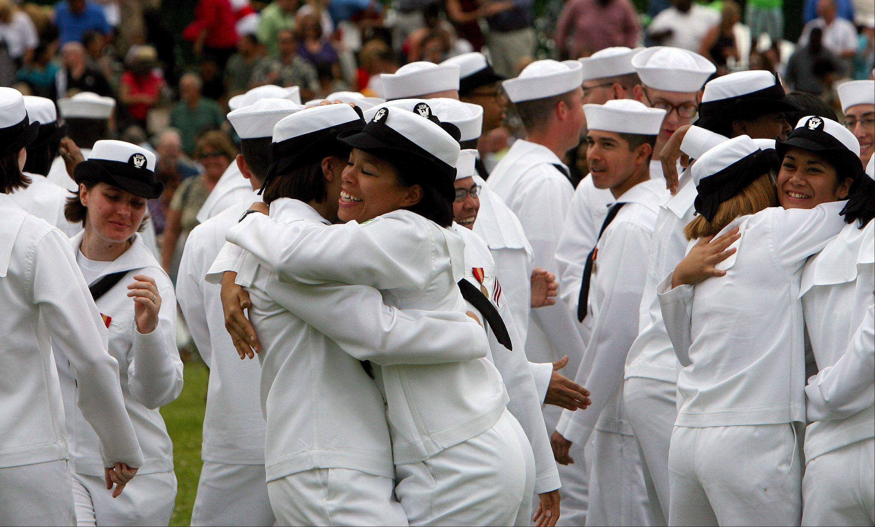 Former recruits, now sailors, embrace after graduation ceremonies at Great Lakes Naval Station Friday. About 1,000 recruits graduated on its 100th anniversary.