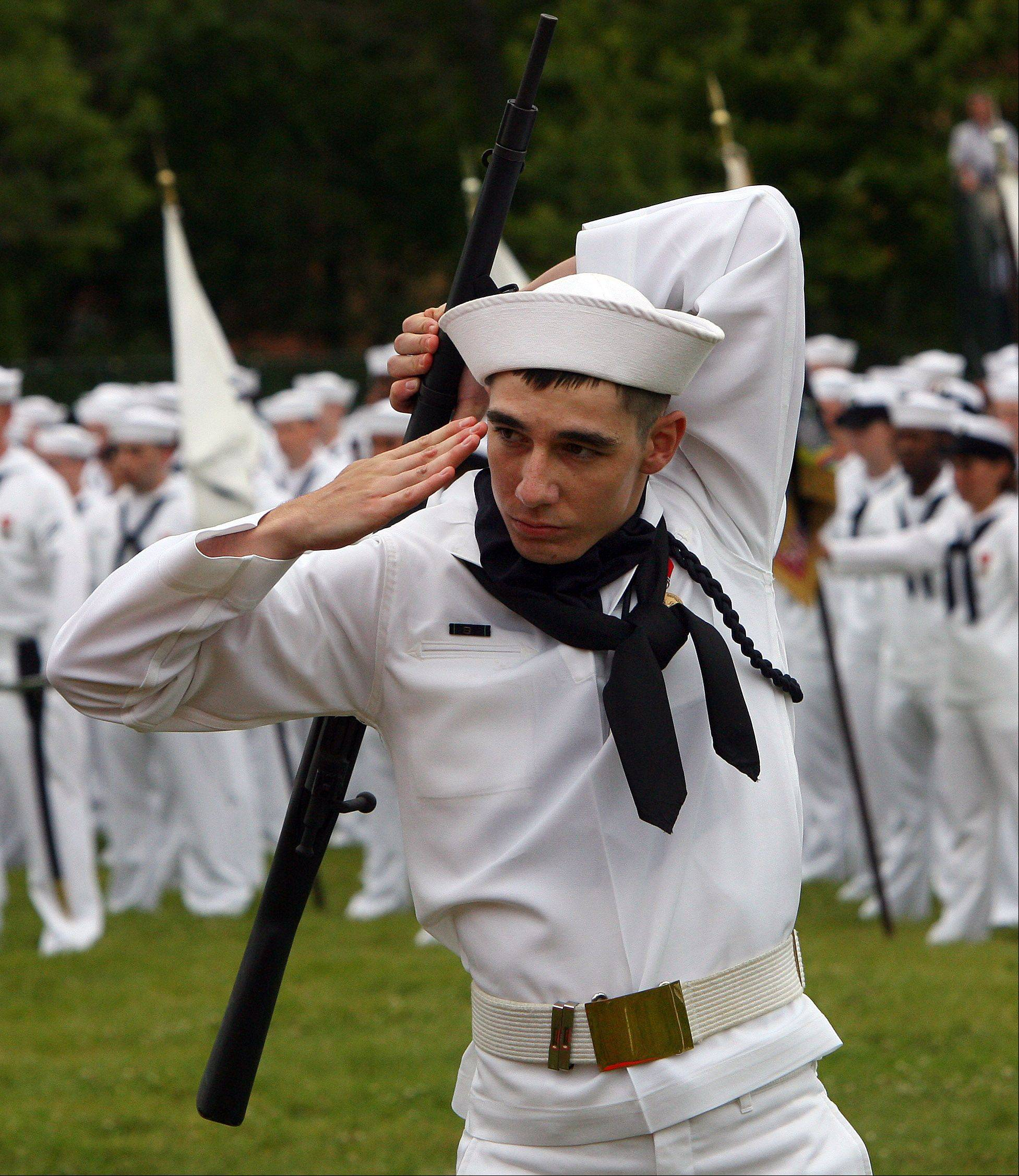 A recruit performs with a show rifle as Great Lakes Naval Station held a rededication ceremony while graduating about 1,000 recruits on its 100th anniversary.