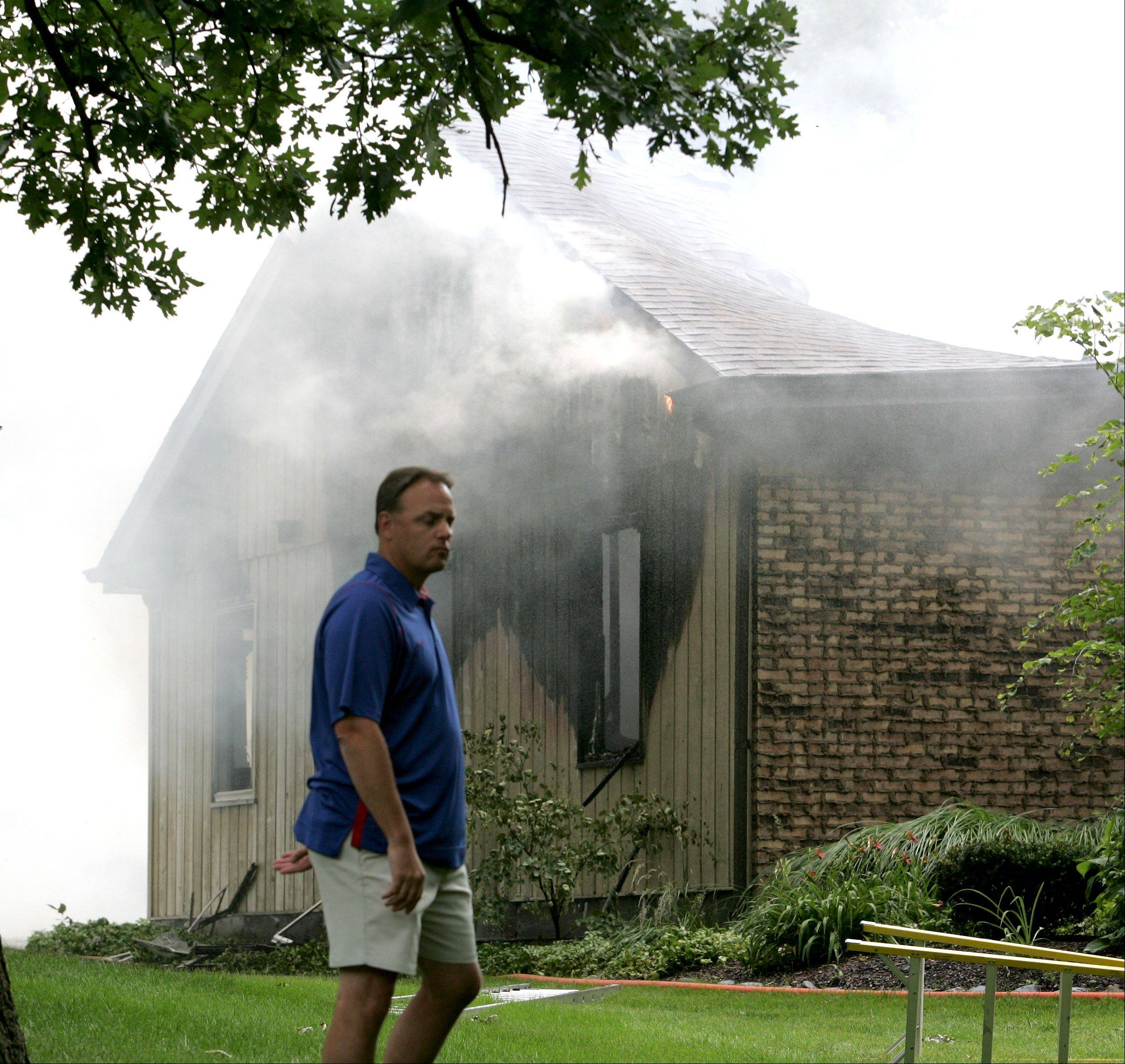 John Chitkowski surveys the damage of his house Friday as it burns on Red Oak Drive in an unincorporated area near Glen Ellyn.
