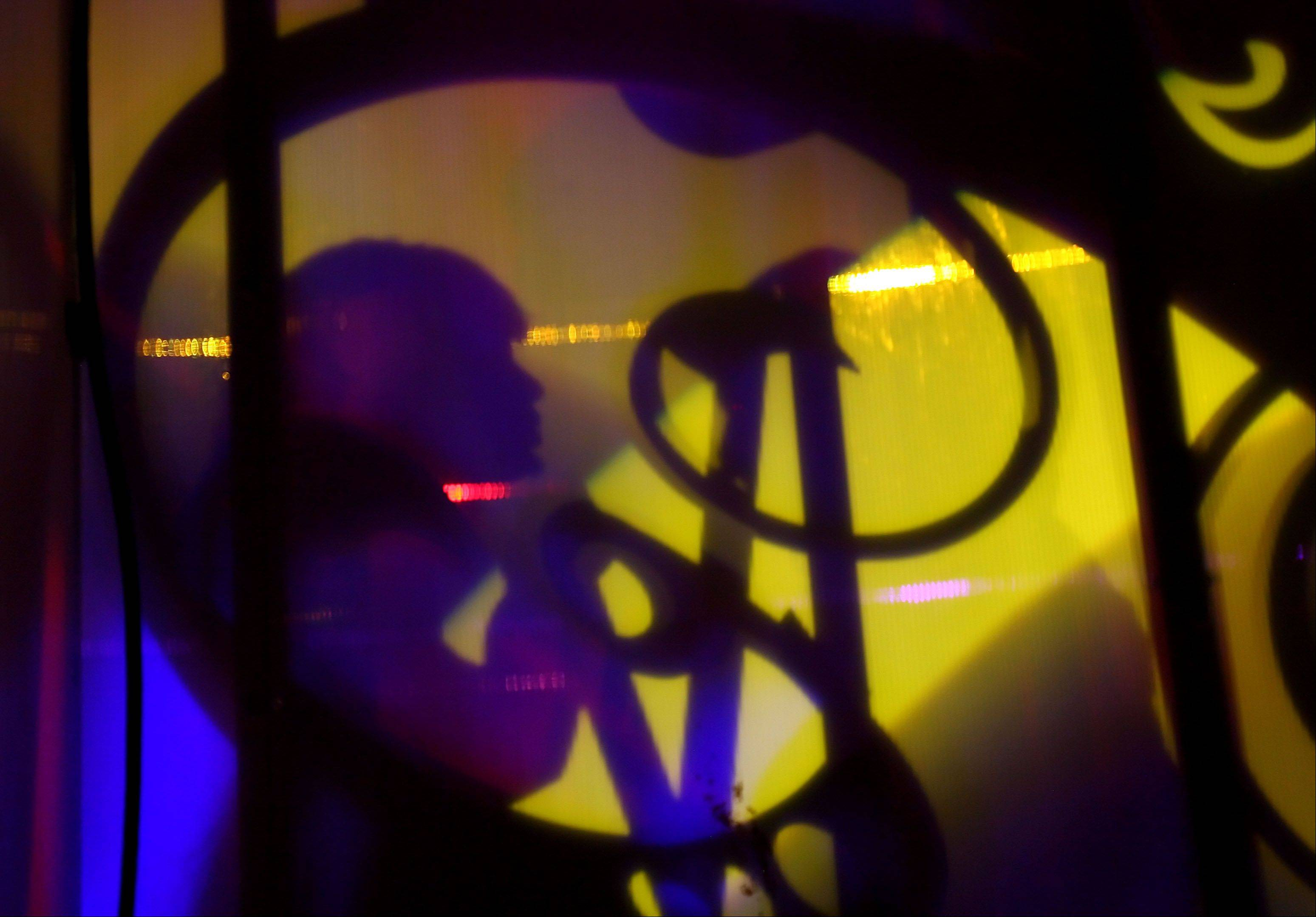 A cast member is silhouetted against the stage background during a production of Pop Fusion at Six Flags amusement park in Gurnee.