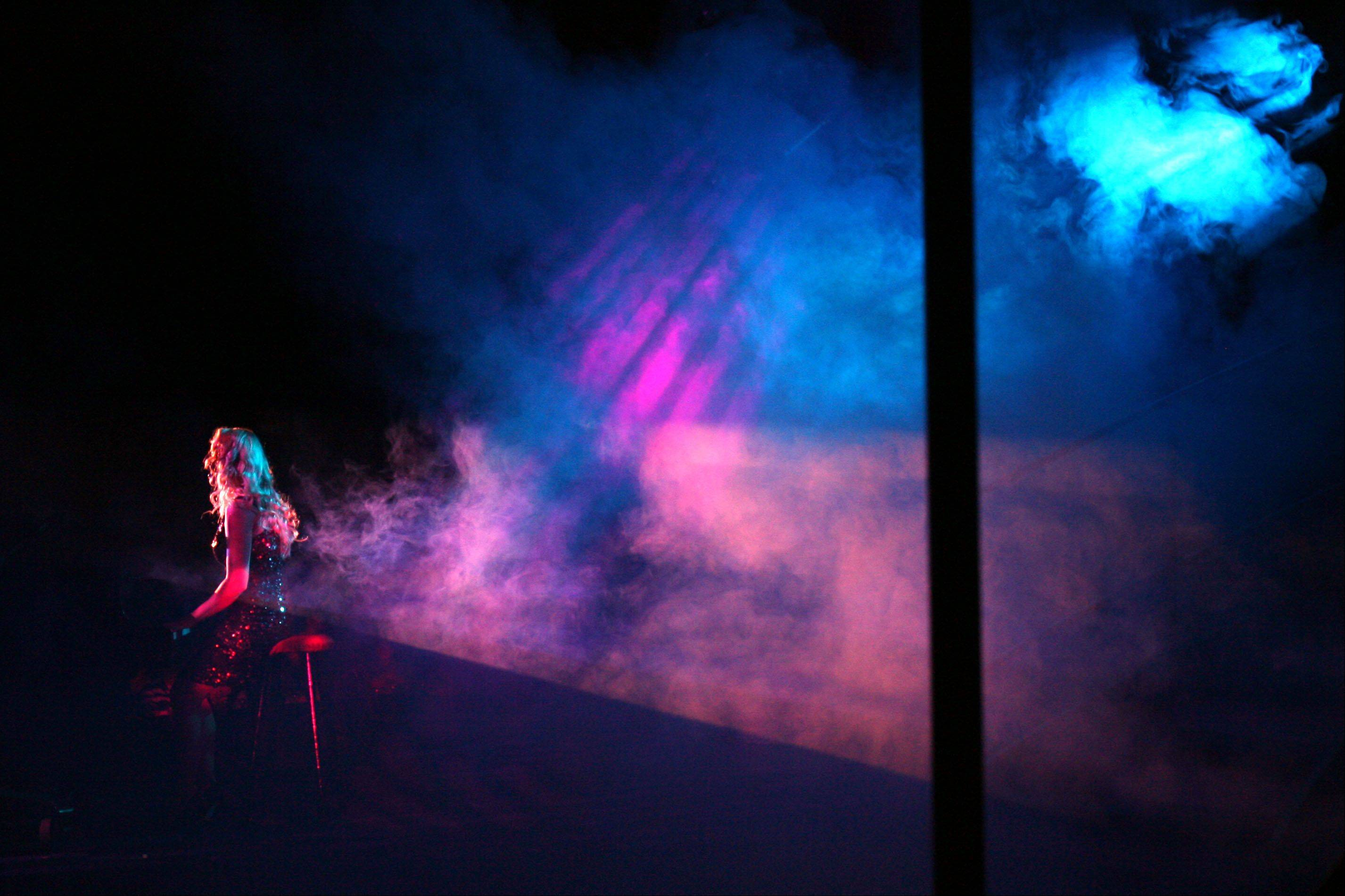 Smoke billows down from the rafters as performer Charissa Hope of Chicago sings during a production of Pop Fusion at Six Flags.