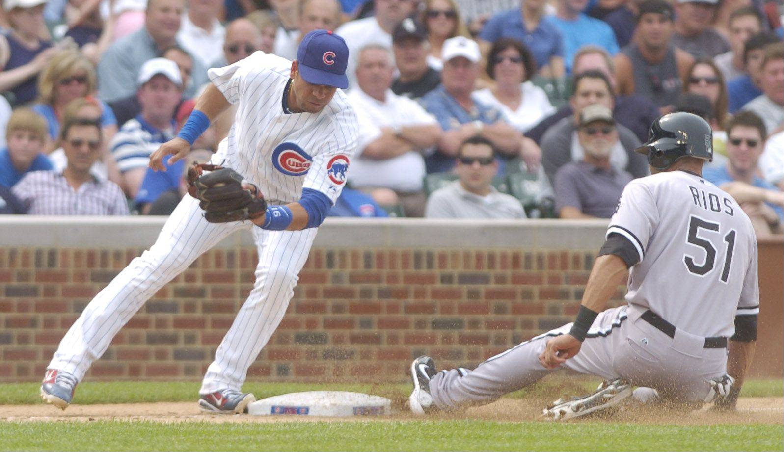 Alex Rios of the White Sox steals third base ahead of the tag by Cubs third baseman Aramis Ramirez during the ninth inning at Wrigley Field Friday.
